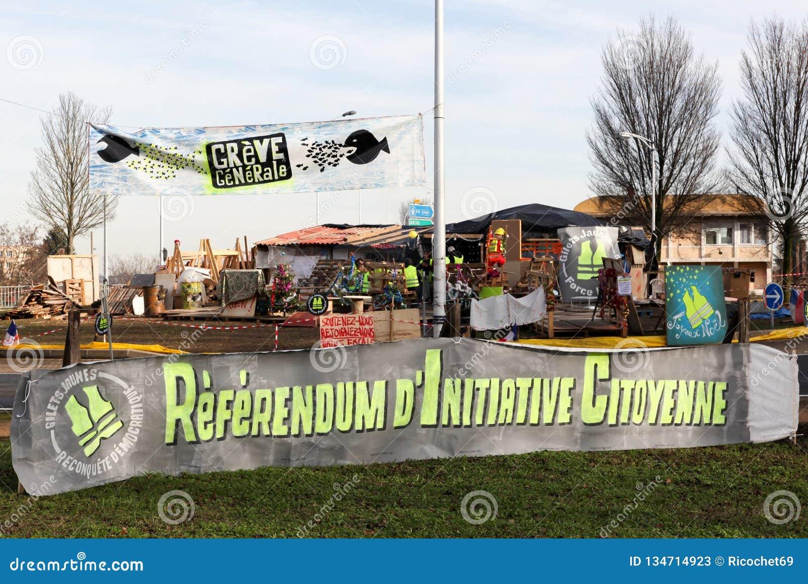 De gele vesten protesteren in Frankrijk bij een ronde cirkel en het vragen om de referenda van het burgersinitiatief genoemd RIC