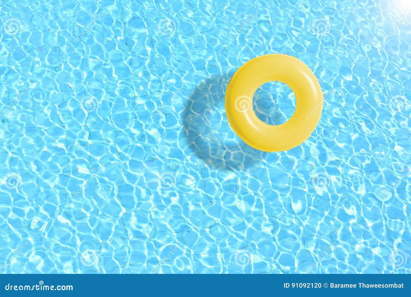 De gele vlotter van de zwembadring in blauw water