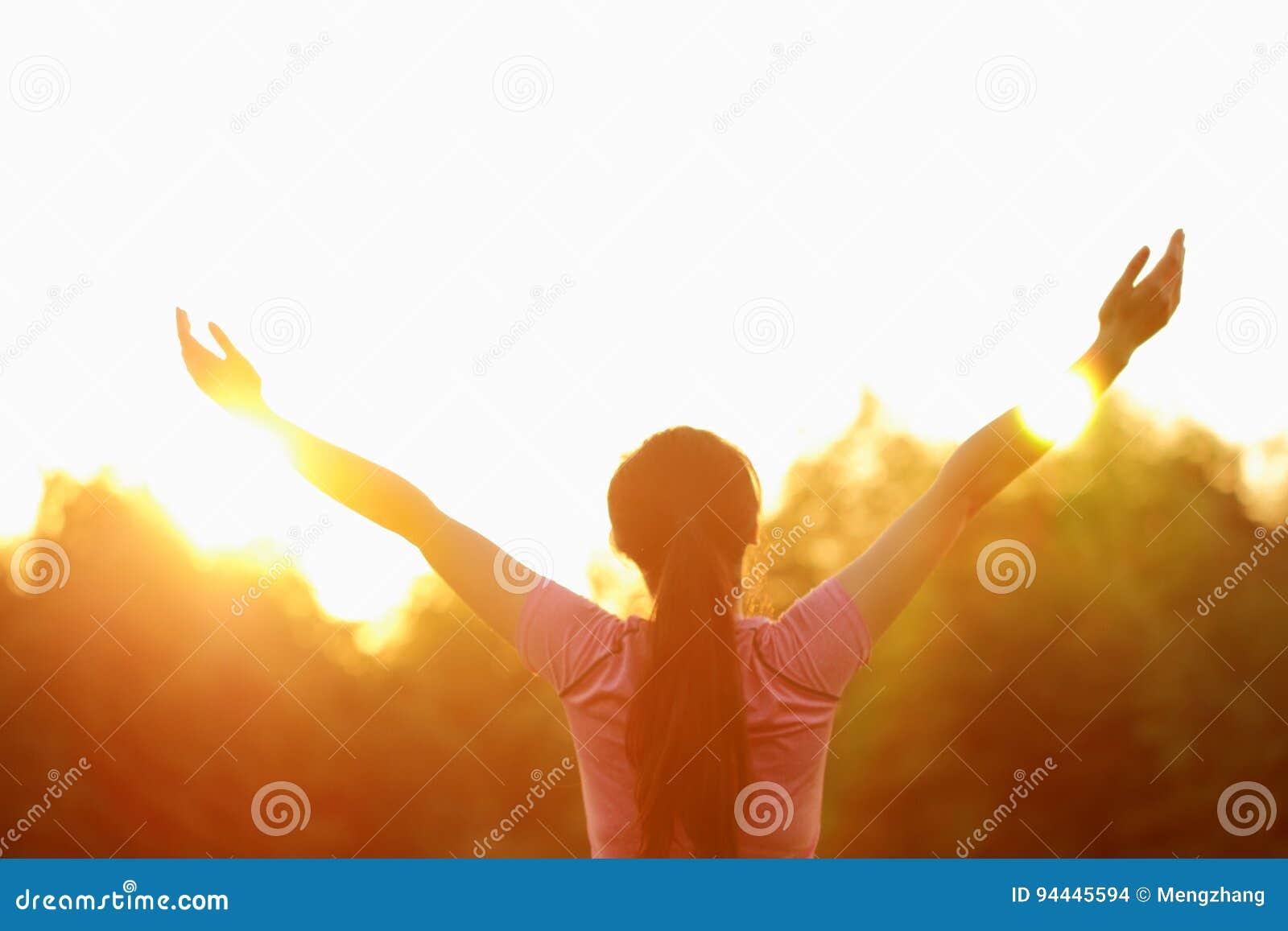 De gelukkige Aziatische Chinese vrouw omhelst aard en zon