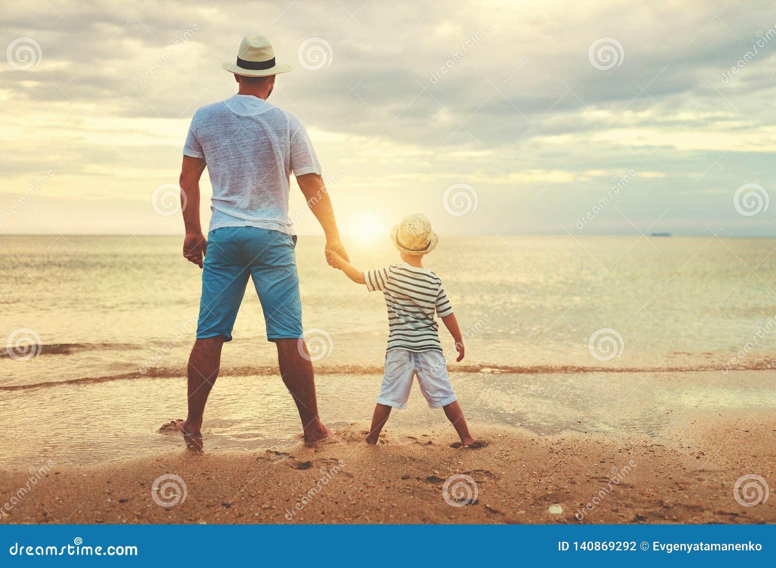 De gelukkige Dag van Vaders familiepapa en kindzoon bij strand