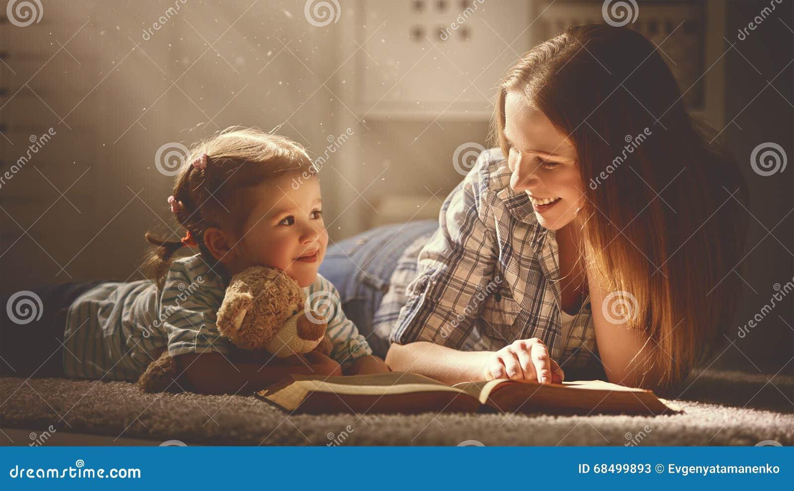 De gelukkige de familiemoeder en dochter lezen een boek in avond