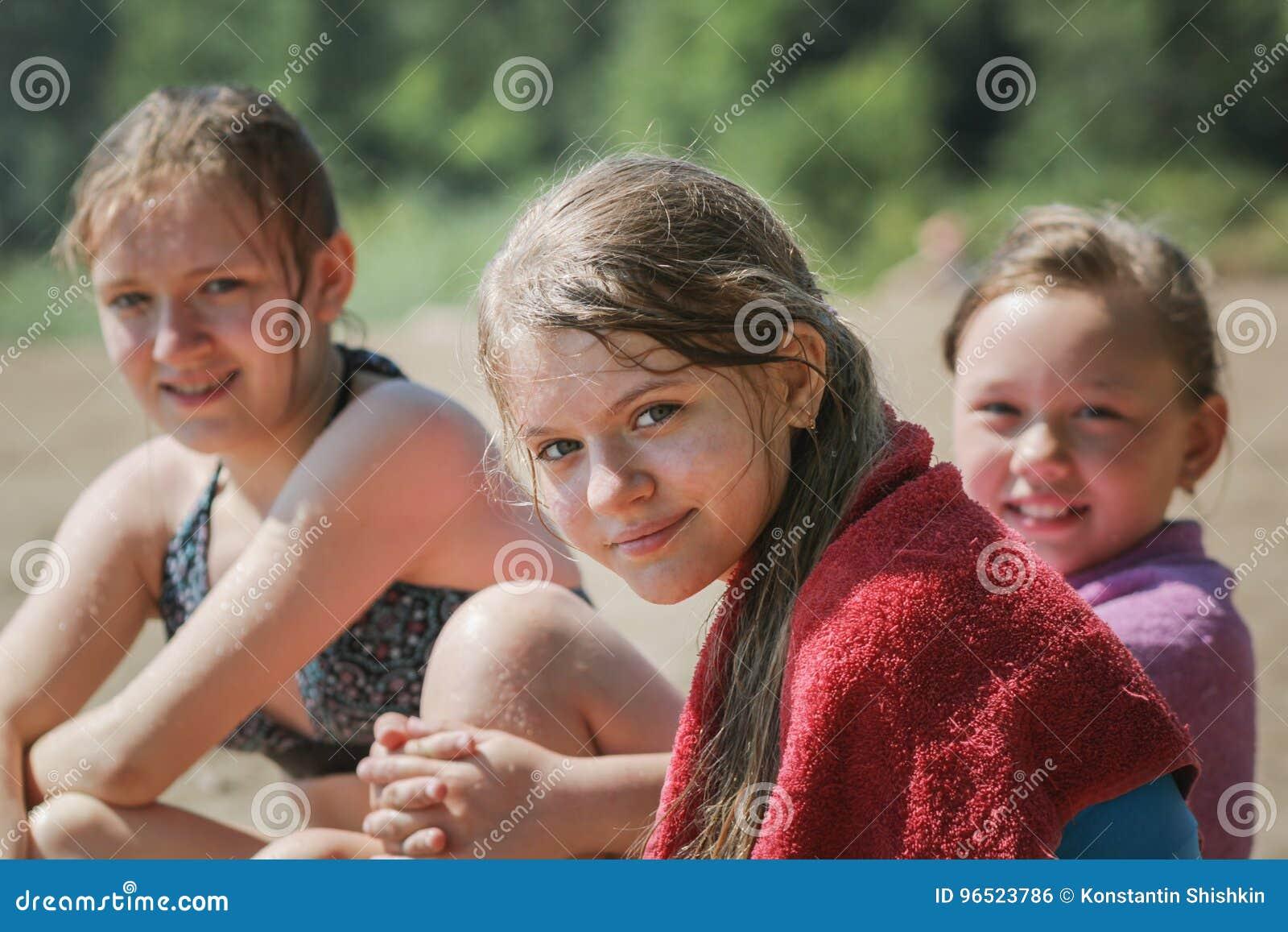 De gelukkige drie meisjes van tienervrienden op strand na het zwemmen