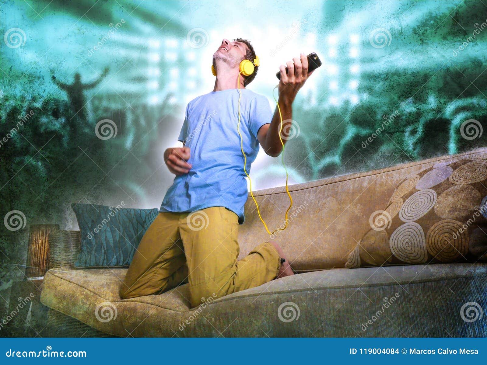 De gelukkige en opgewekte mens die op banklaag springen die aan muziek die met mobiele telefoon en hoofdtelefoons luisteren gekke