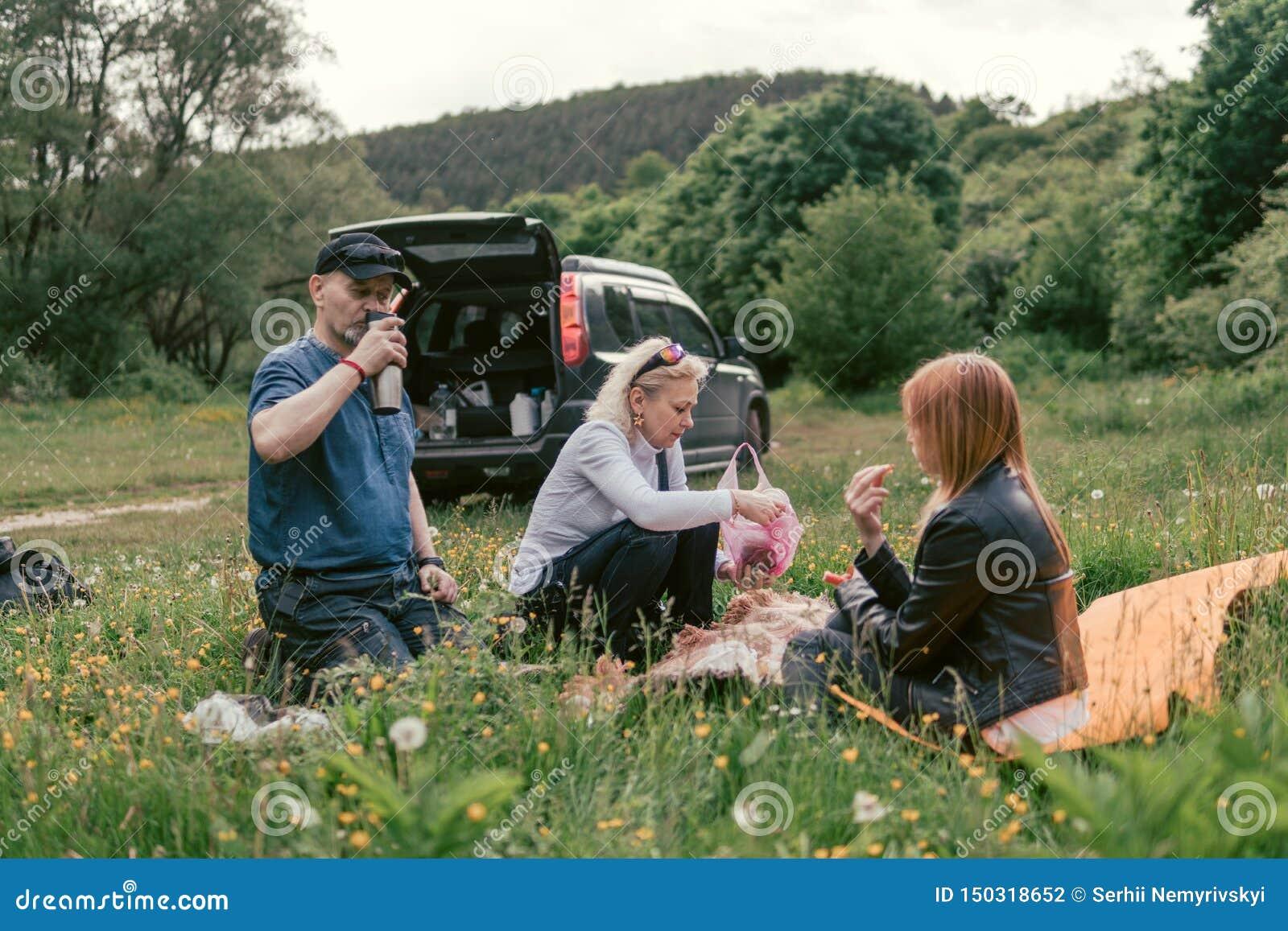 De gelukkige familie die lunch hebben en drinkt thee het kamperen, weekend, picknick man, vrouw, meisje, Oversteekplaats, SUV-aut