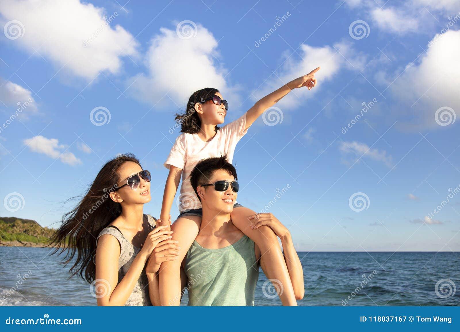De gelukkige familie die zich op het strand bevinden let op de zonsondergang