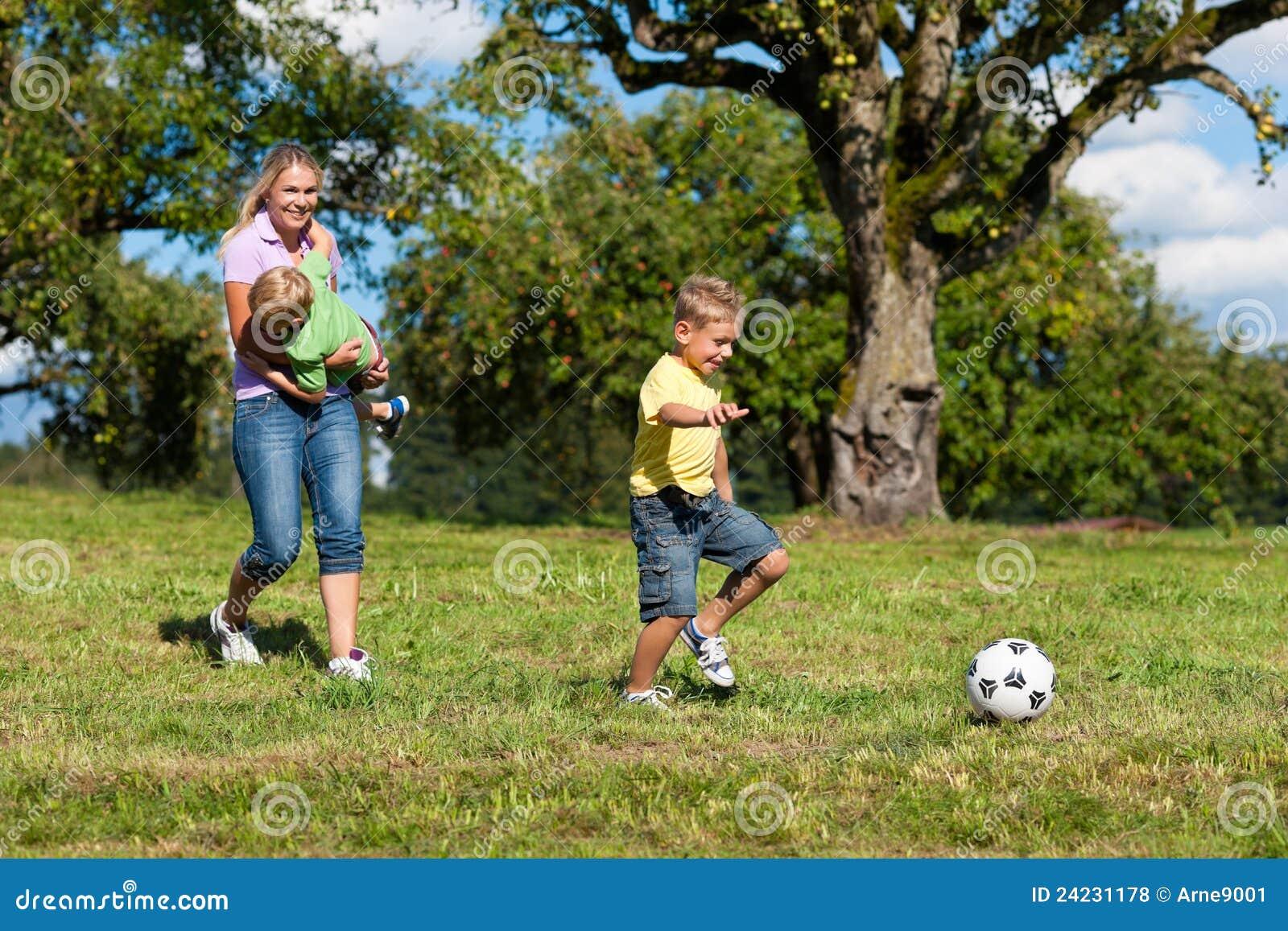 De gelukkige familie speelt voetbal in de zomer
