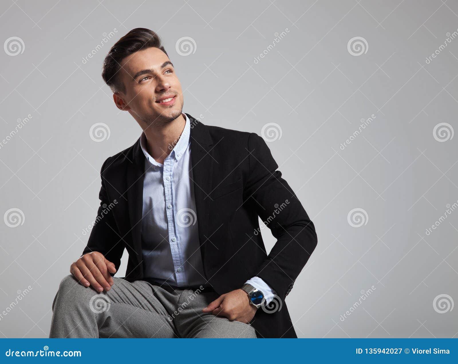 De gelukkige gezette zakenman in zwart kostuum kijkt omhoog aan kant