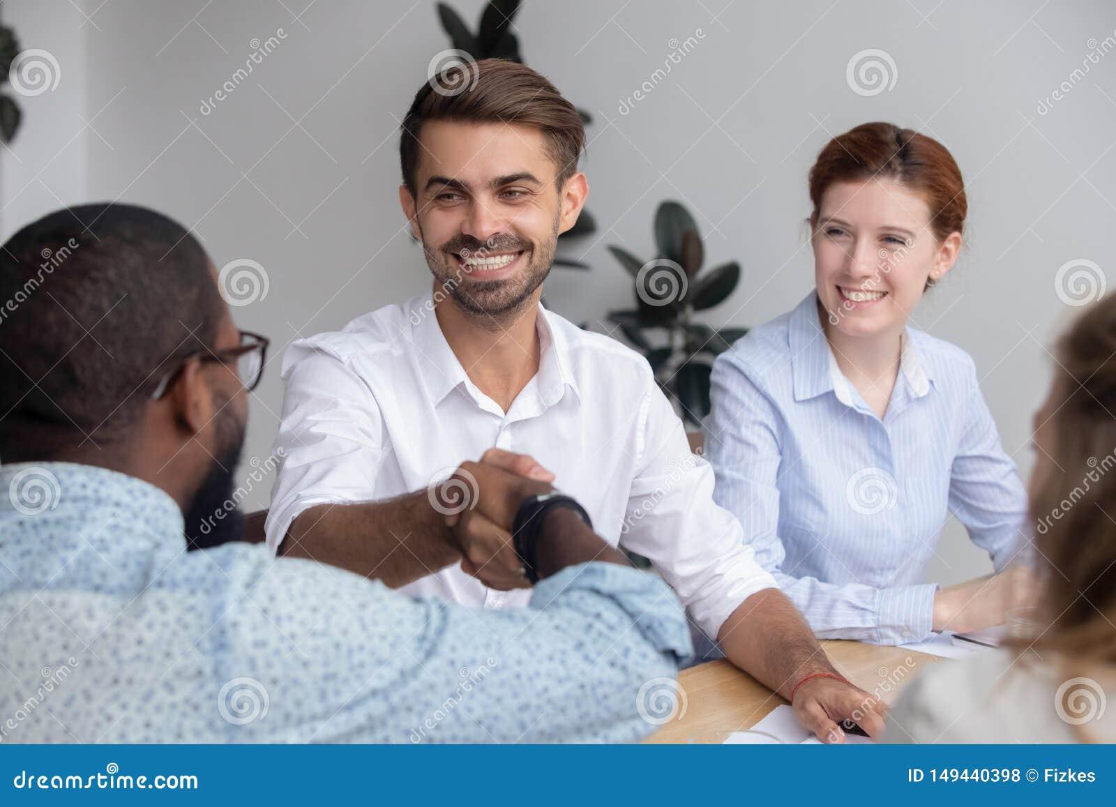 De gelukkige glimlachende Kaukasische mannelijke collega van Afrikaans-Amerikaan van de manager schuddende hand