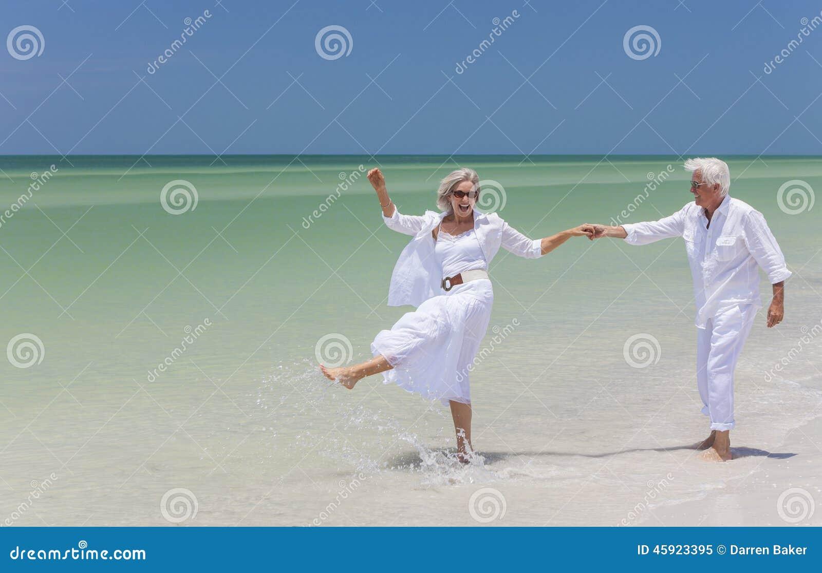 De gelukkige Hogere Handen van de Holding van het Paar Dansende op een Tropisch Strand