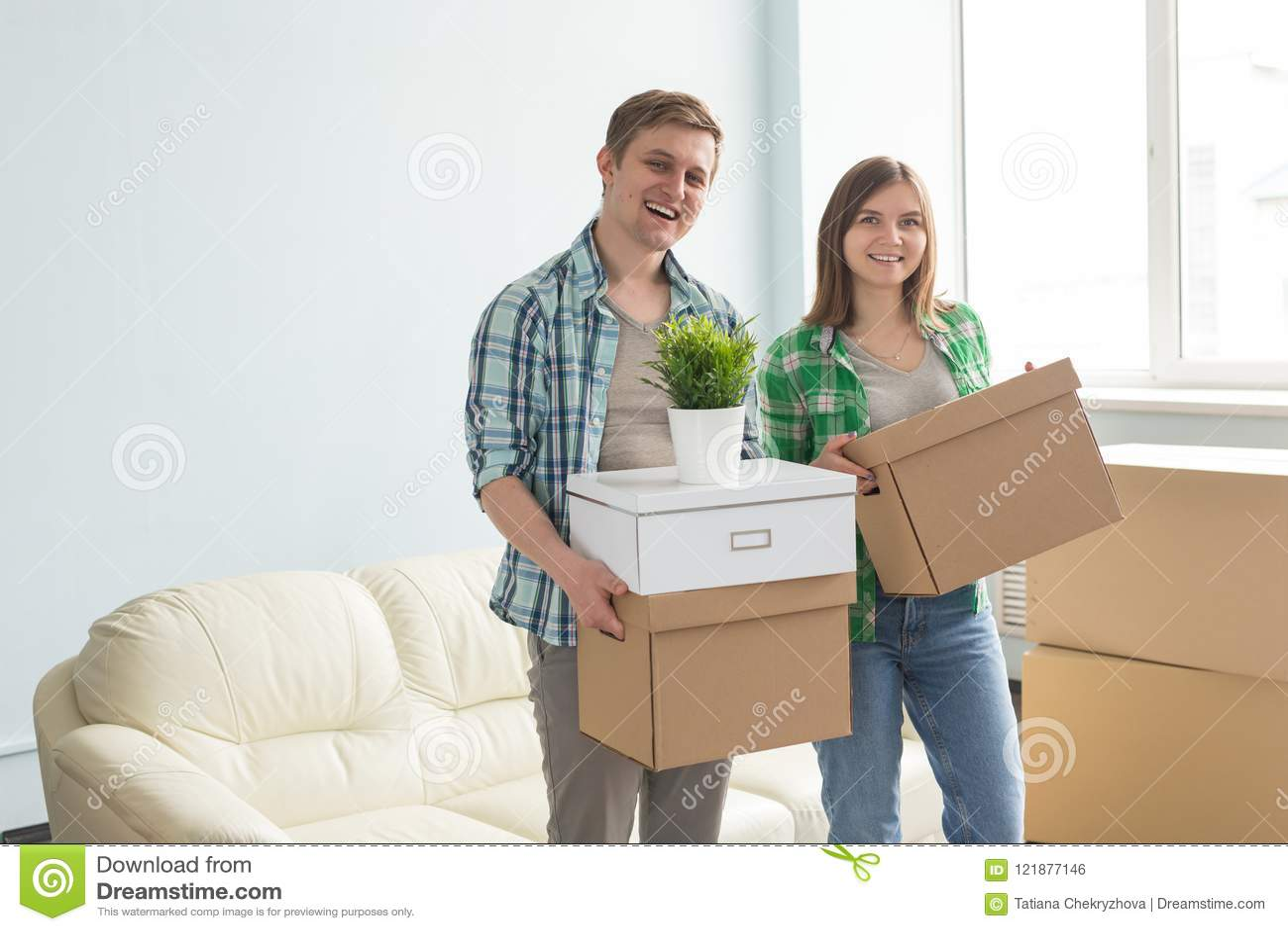 De gelukkige jonge bewegende dozen van de paarholding met bank op de achtergrond