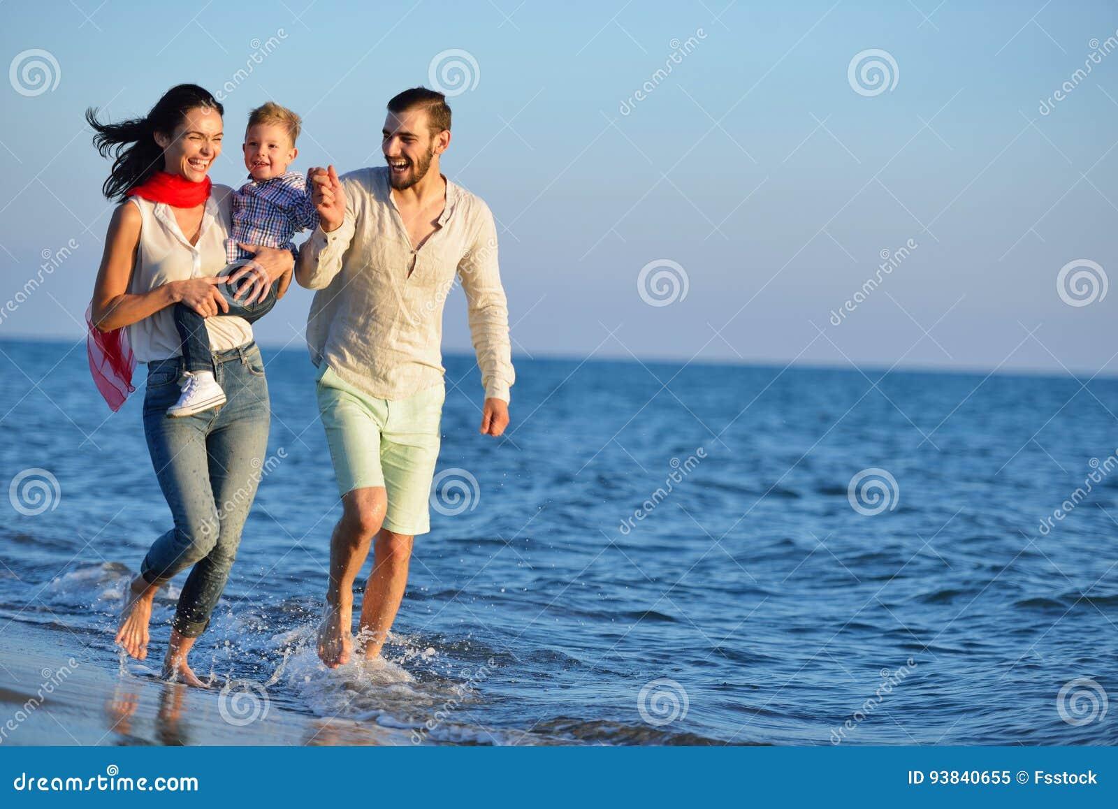 De gelukkige jonge die familie heeft pret op strand en sprong bij zonsondergang in werking wordt gesteld