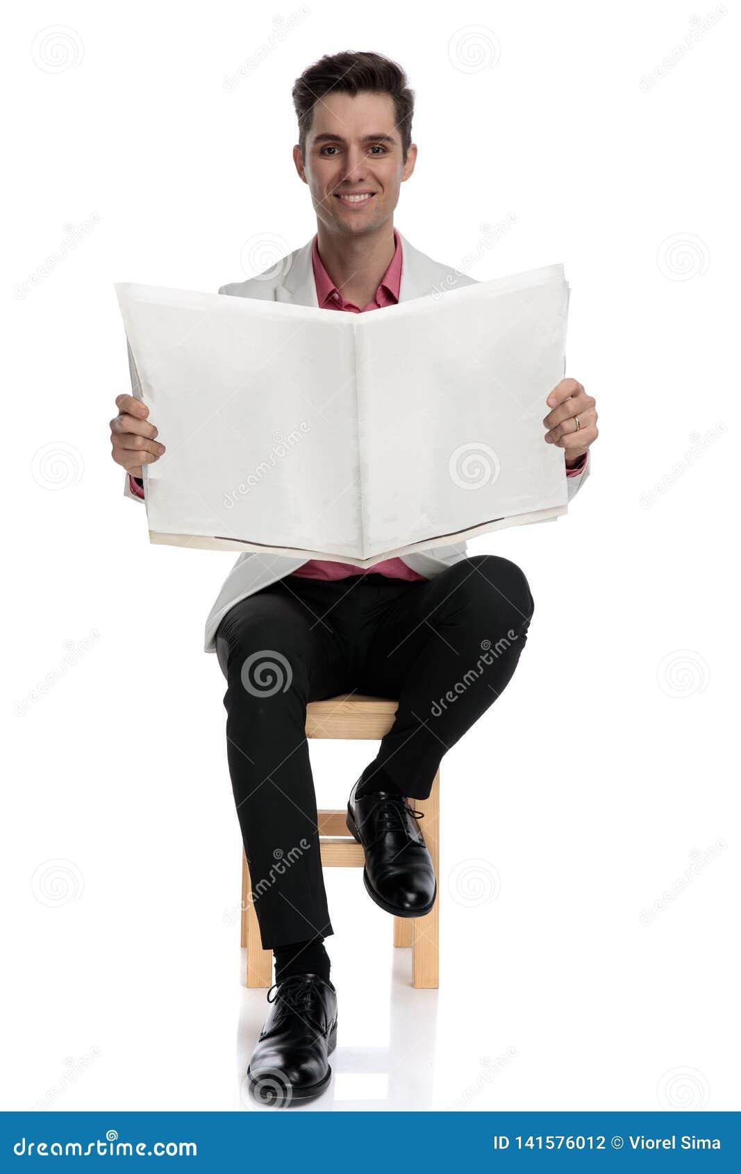 De gelukkige jonge krant van de zakenmanlezing terwijl het zitten