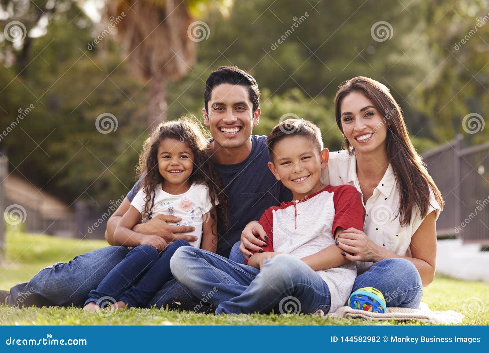 De gelukkige jonge Spaanse familie die het gras in het park zitten die aan camera glimlachen, sluit omhoog