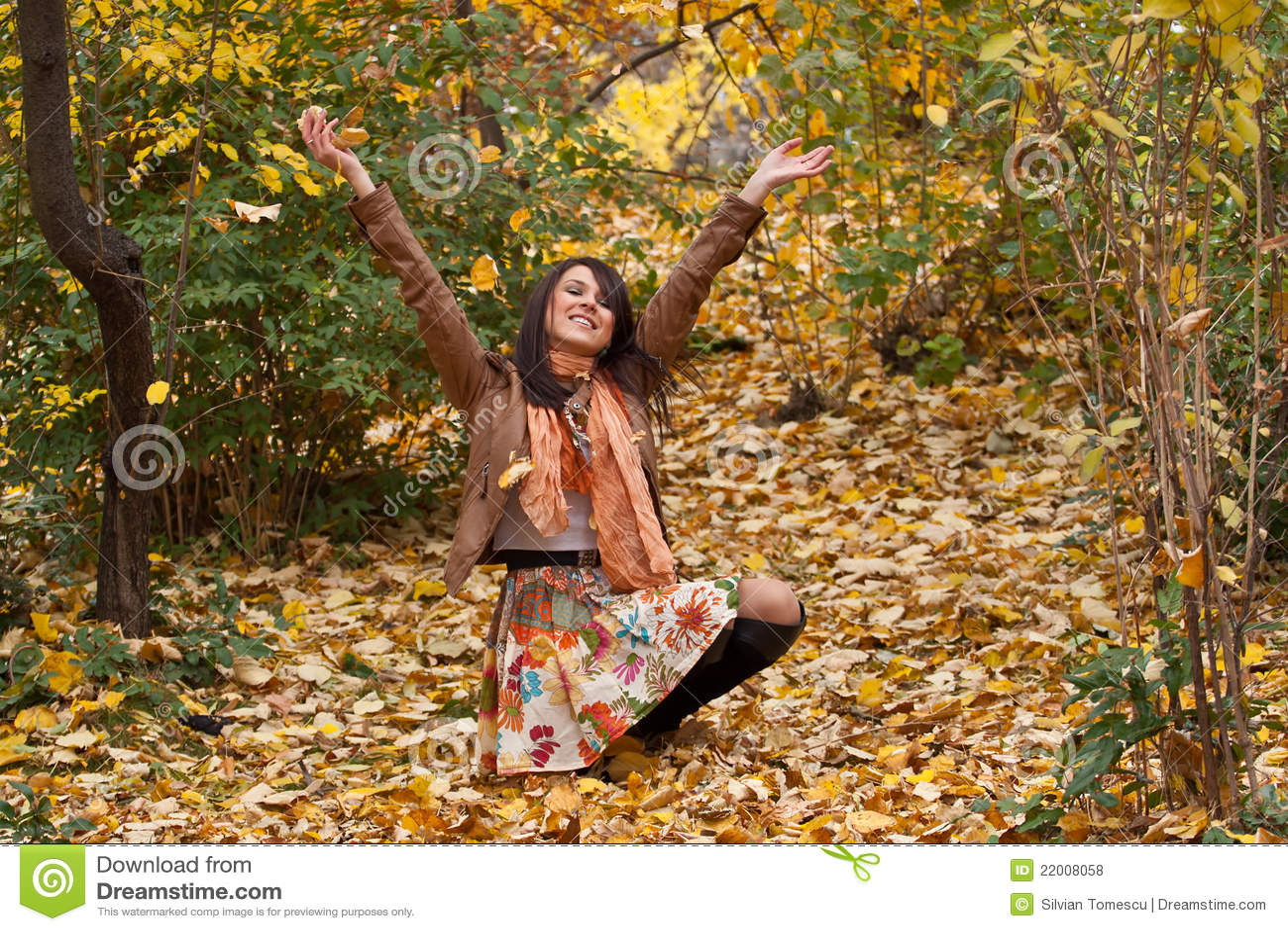 De gelukkige jonge vrouw geniet van de herfst