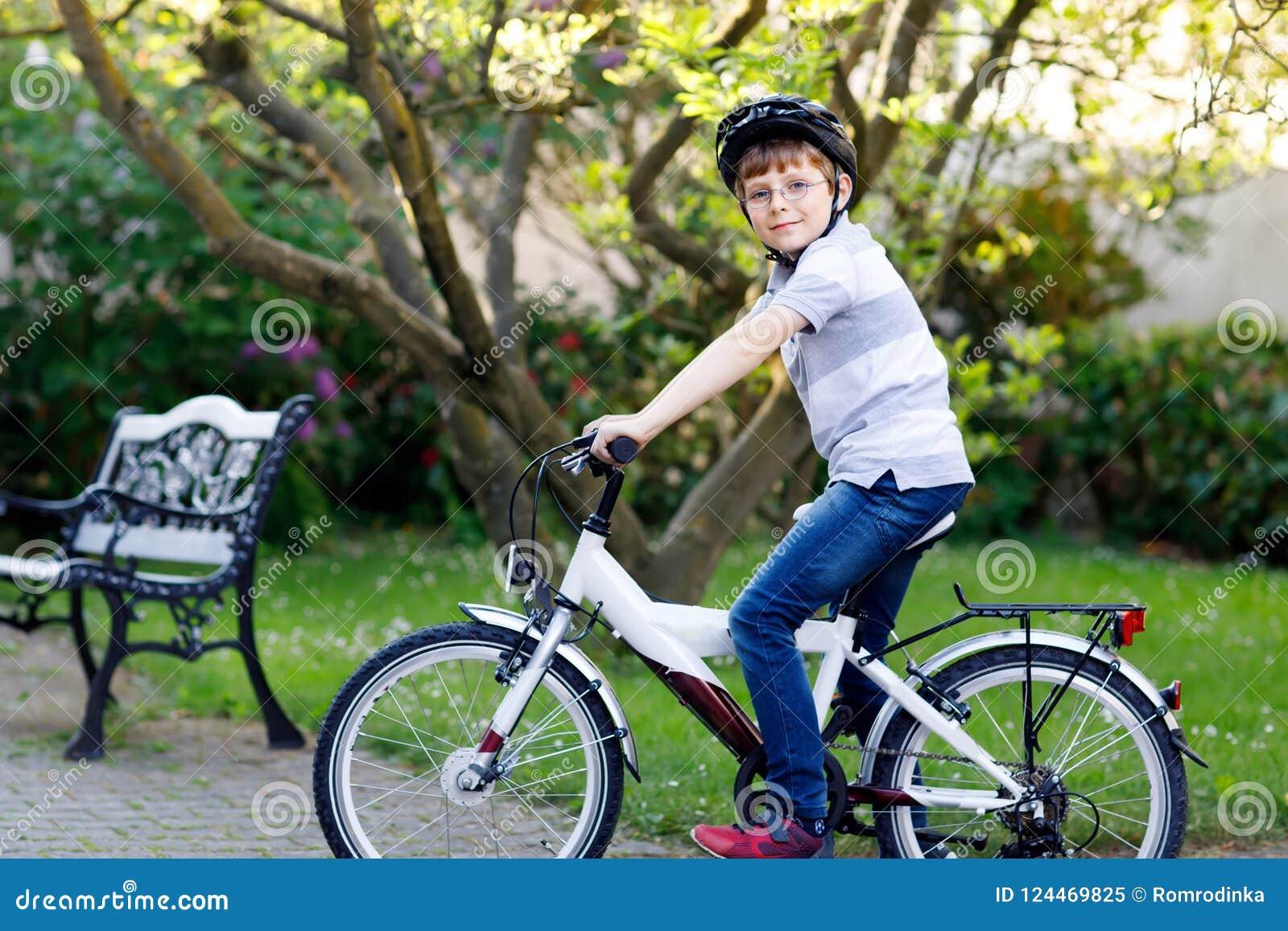 De gelukkige jongen die van het schooljonge geitje pret met het berijden van fiets hebben Actief gezond kind die met veiligheidsh