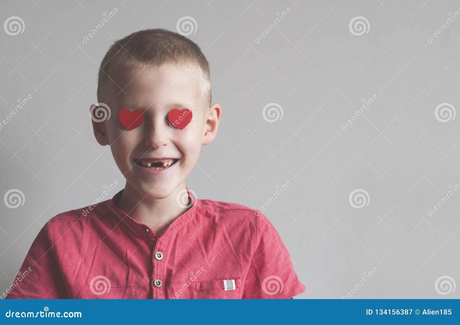 De gelukkige jongen met hartvorm het houden van kijkt