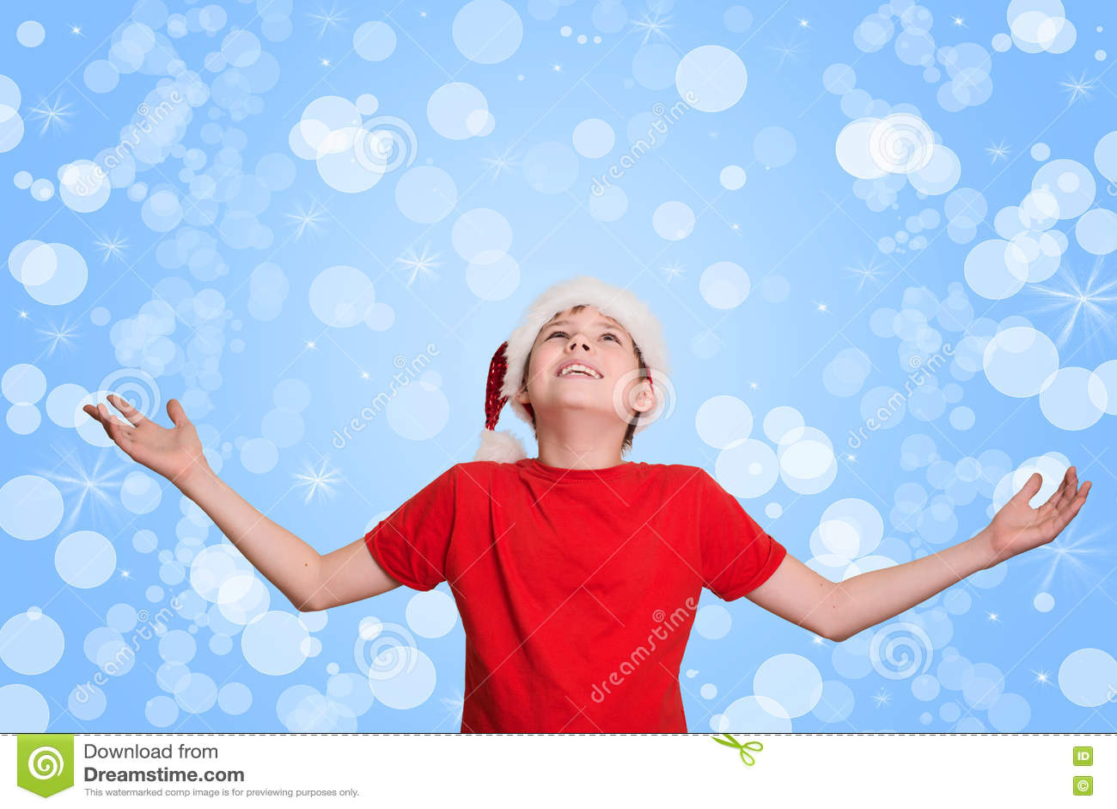 De gelukkige jongen overhandigt op het wachten op Kerstmis Het glimlachen van jong geitje in santa h