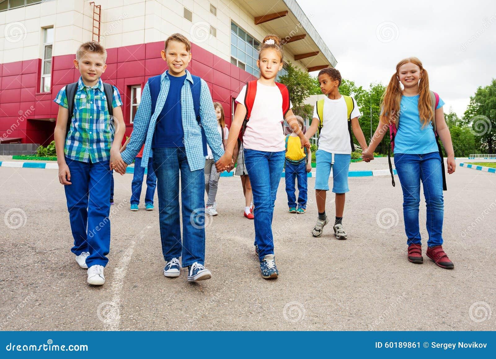 De gelukkige kinderen dragen rugzakken, gang dichtbij school