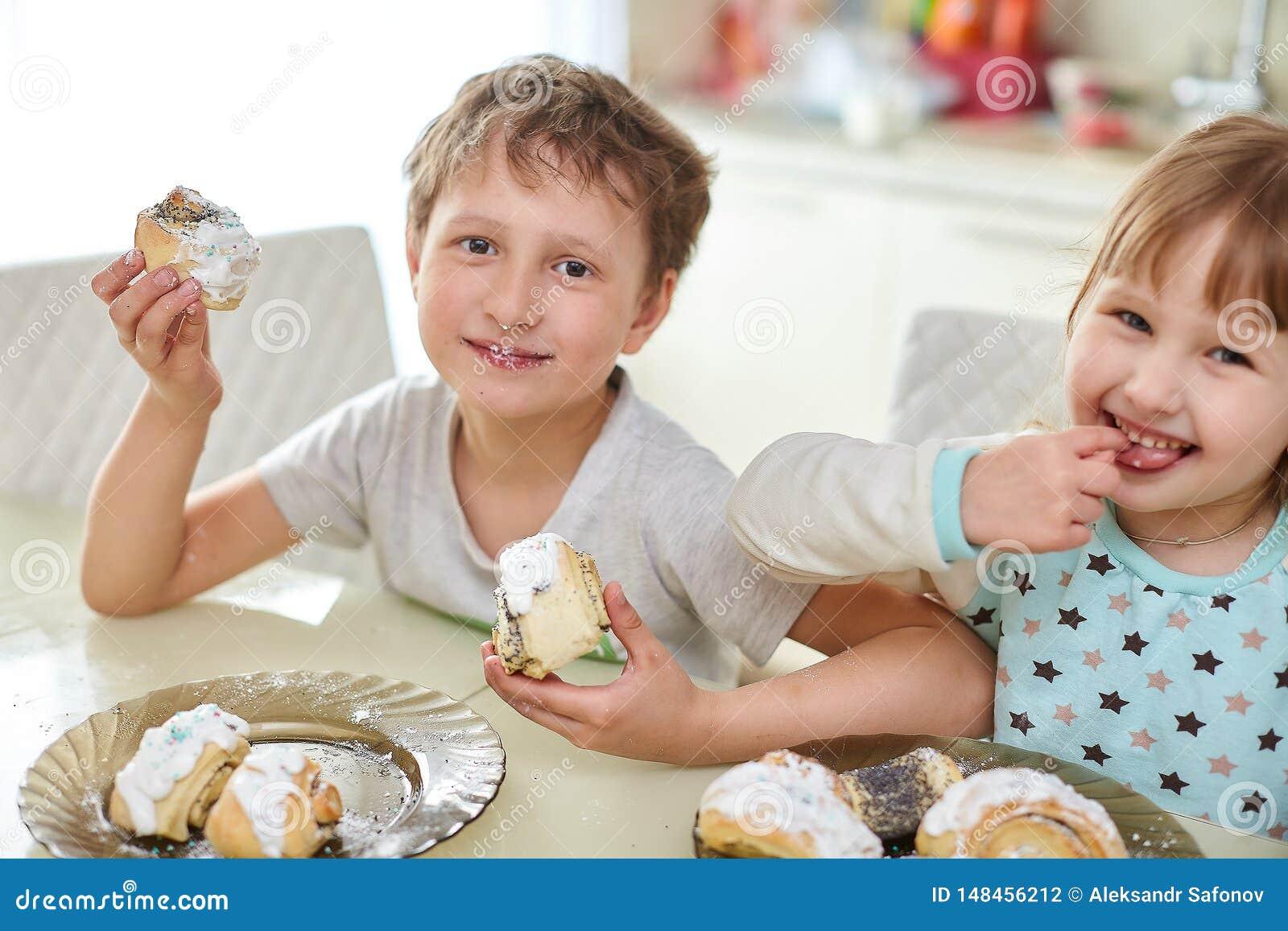 De gelukkige kinderen eten gebakjes in de heldere keuken bij de lijst