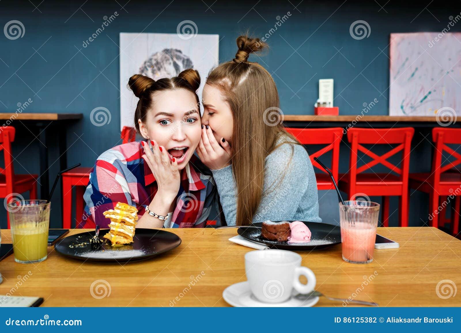 De gelukkige meisjesvrienden hebben kop van koffie in modern stadsrestaurant