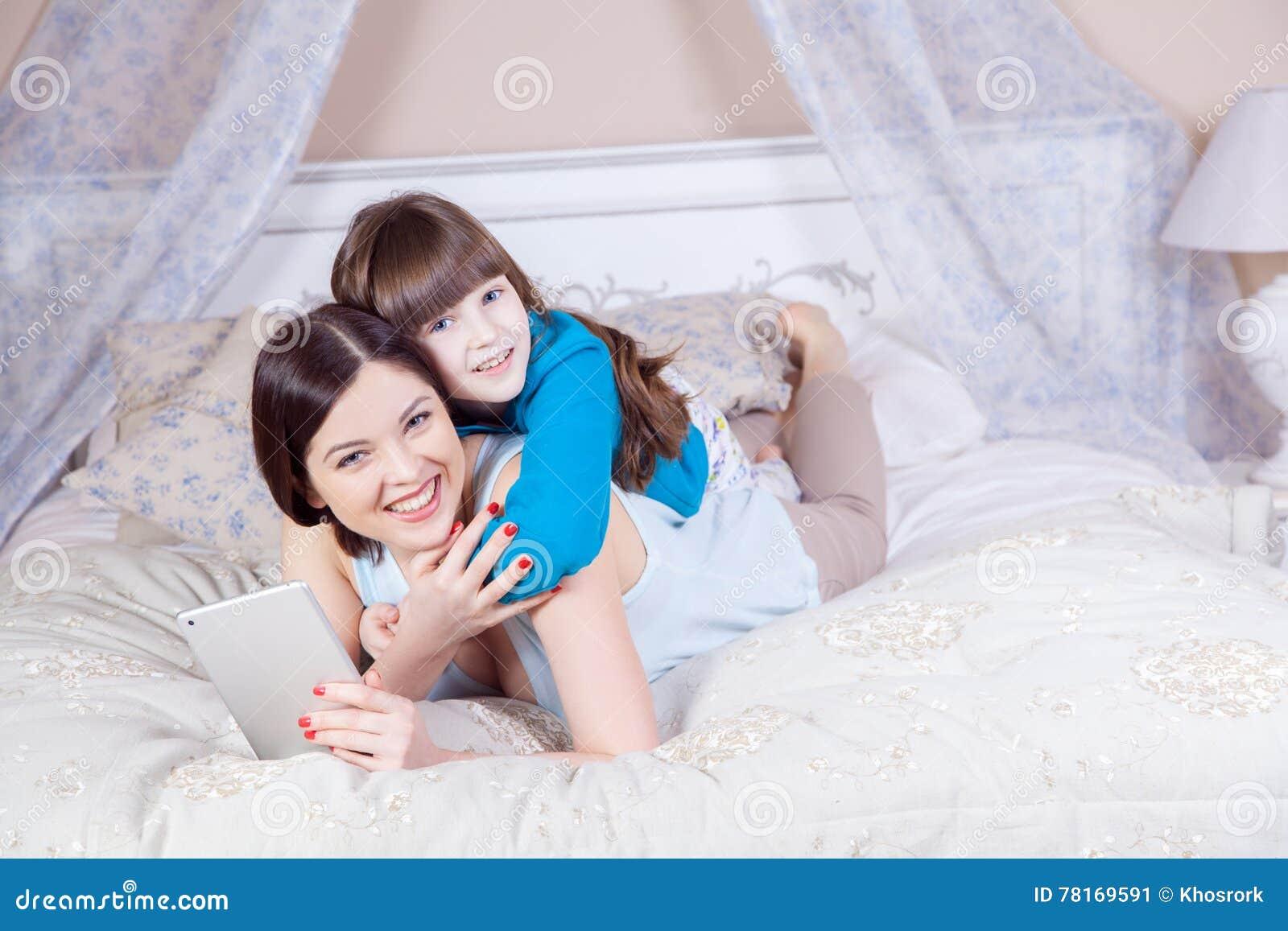 De gelukkige moeder en de dochter lagen in bed met digitale tablet