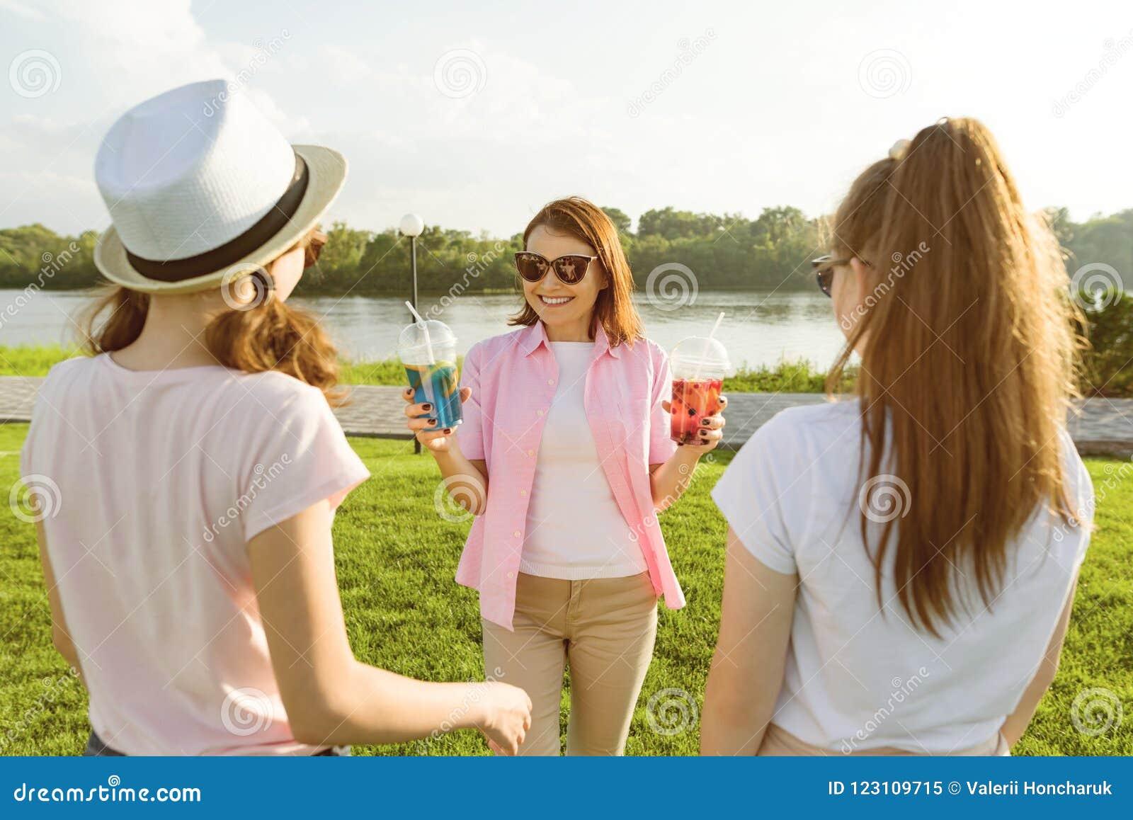 De gelukkige moeder rust actief op aard met haar tienerdochters 14 en 16 jaar oud Mededeling van ouders en teenag
