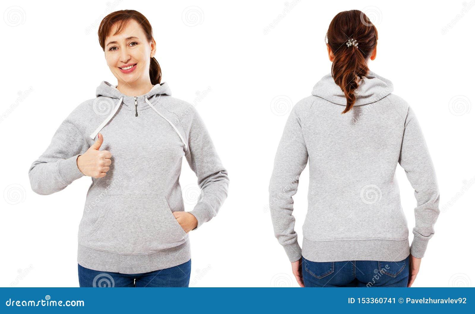 De gelukkige mooie vrouw op middelbare leeftijd in een grijs sweatshirt die als teken tonen, hoodie spot plaatste omhoog