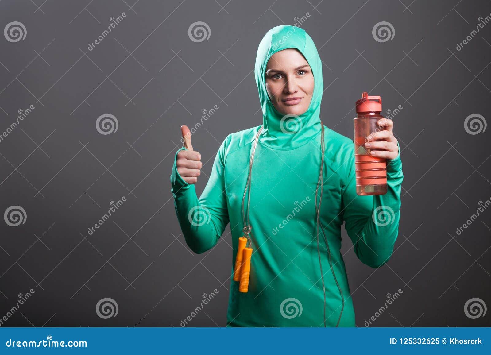 De gelukkige moslimvrouw van de trotsatleet in groene hijab of Islamitische sport