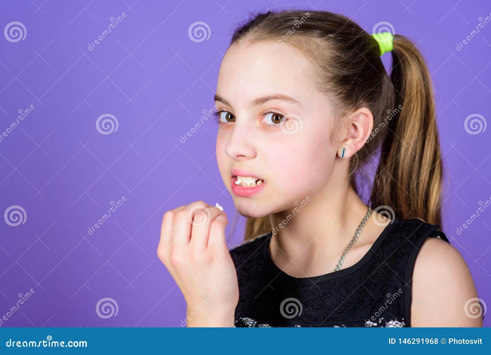 De gelukkige snoepjes en de traktaties van weinig kindliefde Het kleine meisje eet heemst Het op dieet zijn en calorie Zoet tandc