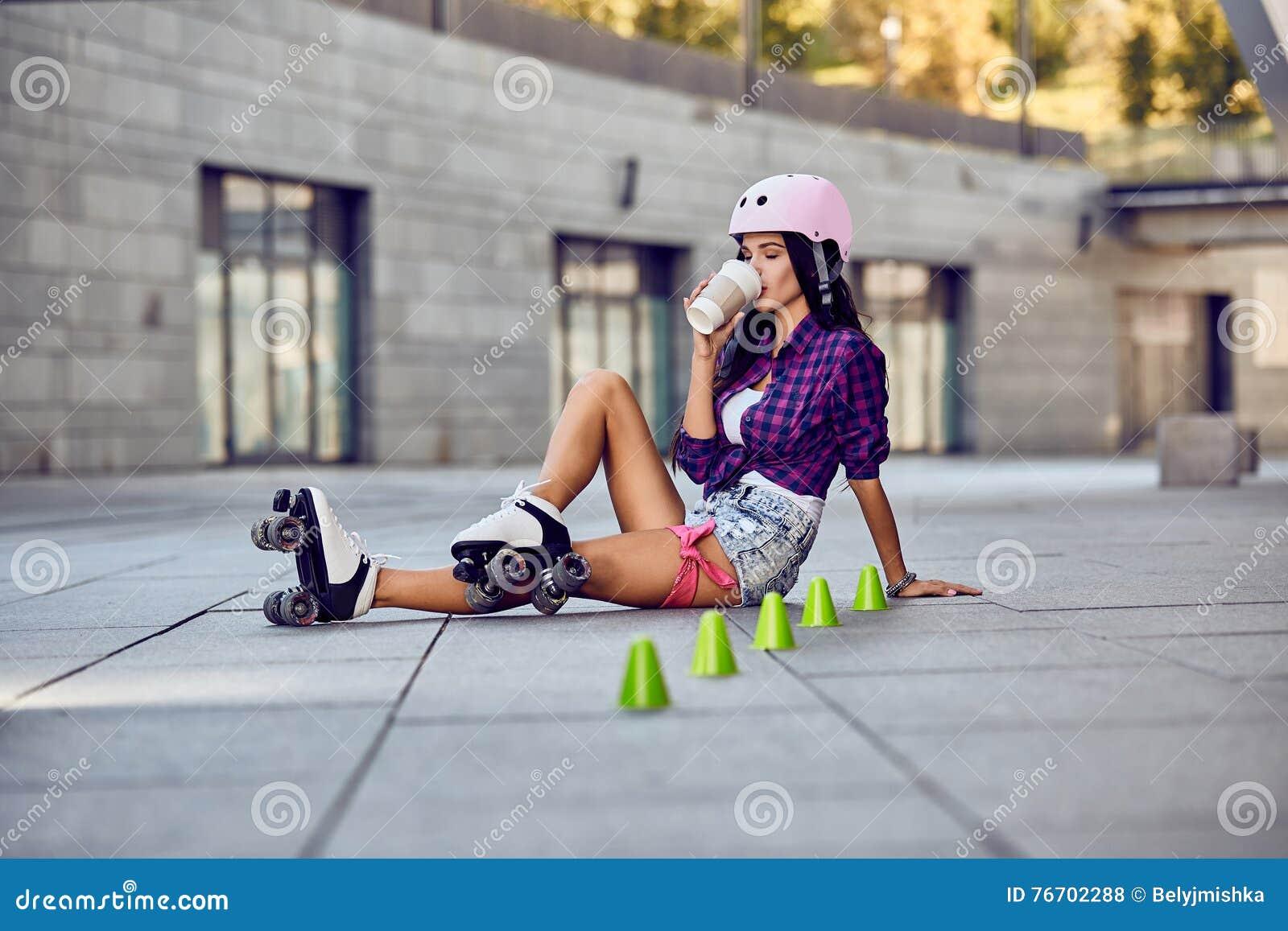 De gelukkige tiener rollerblading zitting op straat en drinkt koffie