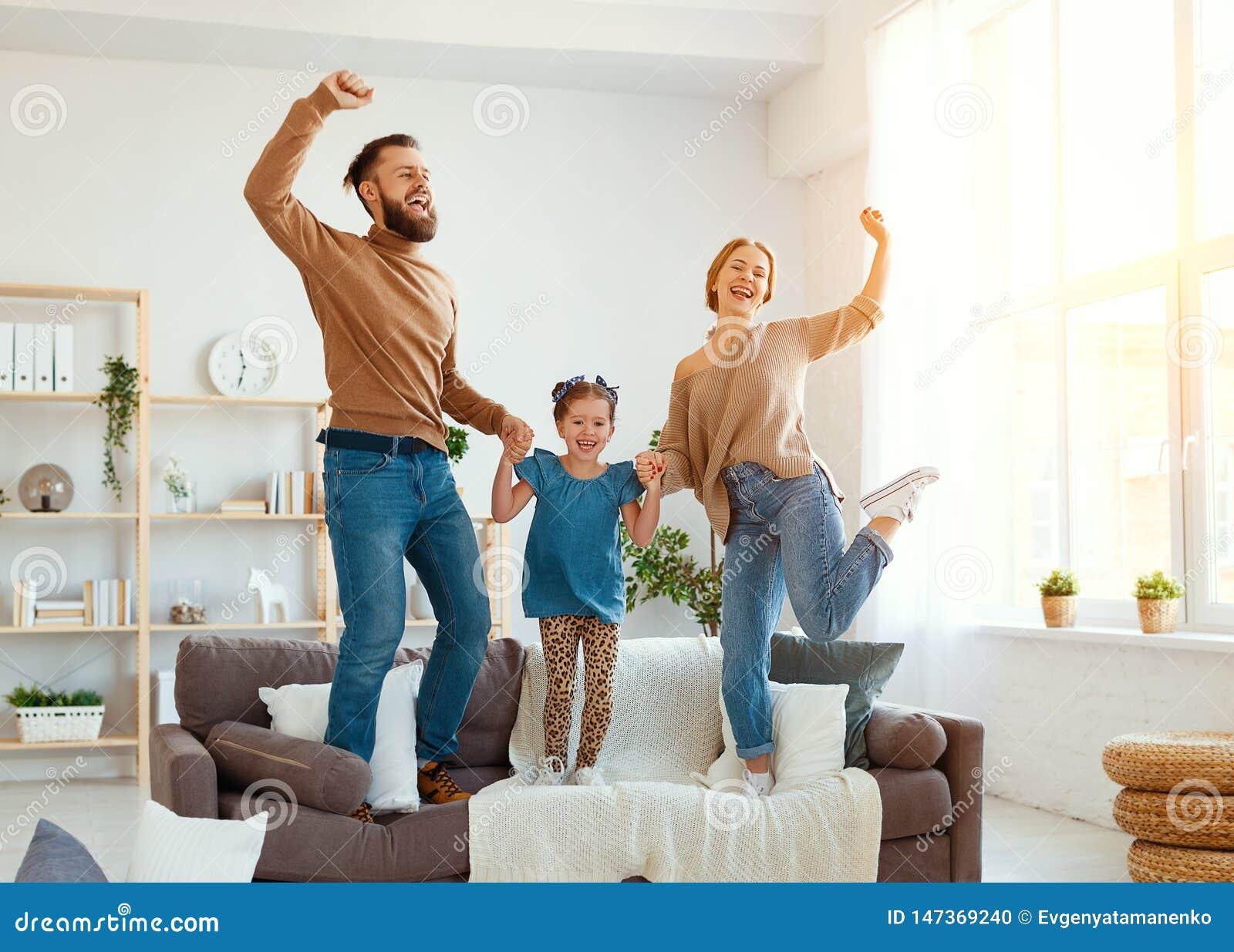 De gelukkige vader van de familiemoeder en kinddochter die thuis dansen