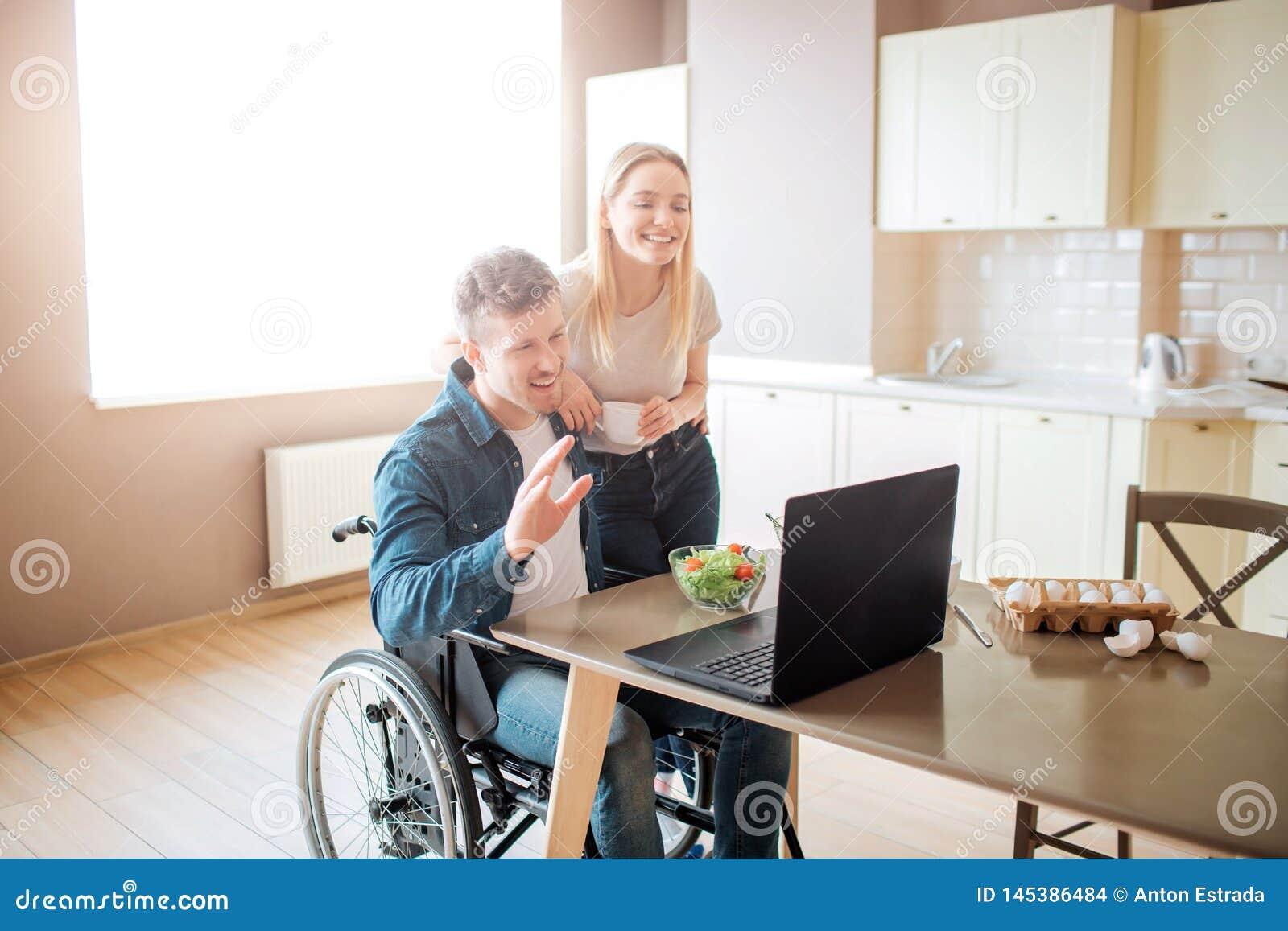 De gelukkige vrolijke jonge mens zit bij lijst en kijkt op laptop Kerel met onbekwaamheid en inclusiviteit Jonge vrouwentribune
