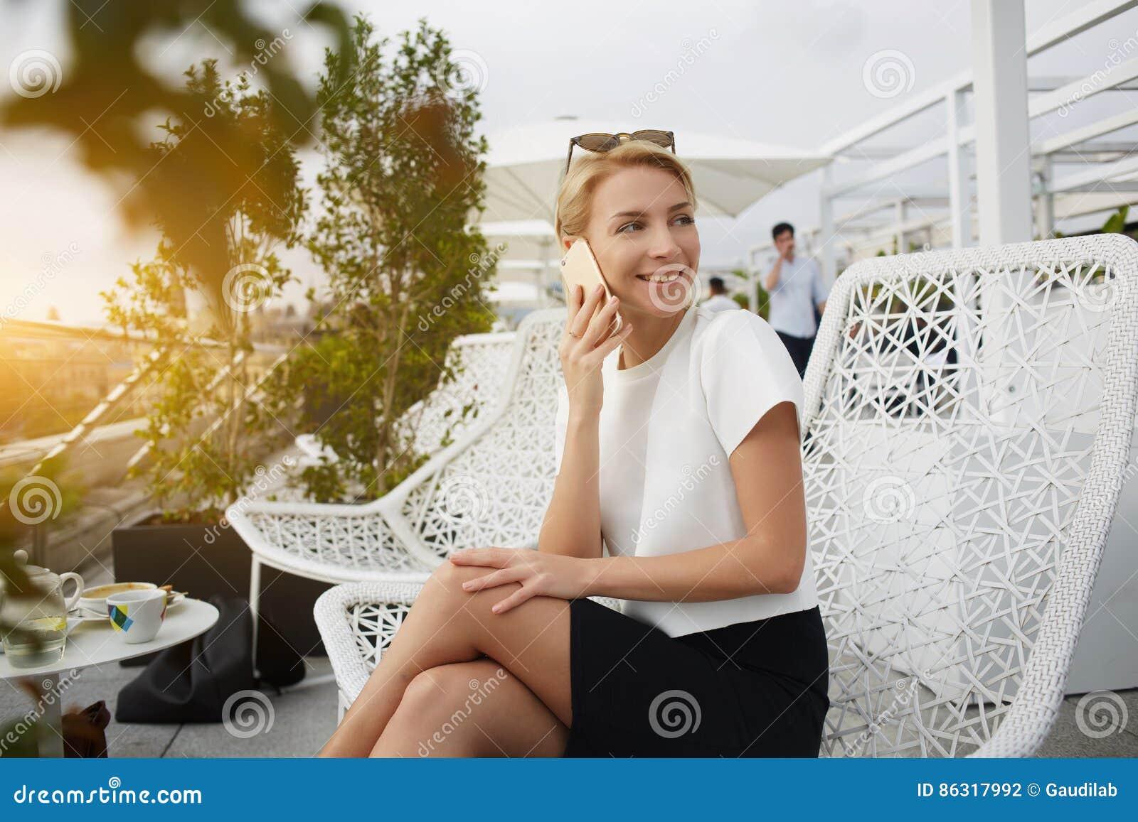 De gelukkige vrouw glimlacht vijand iemand, terwijl op celtelefoon tijdens rust in koffie spreekt