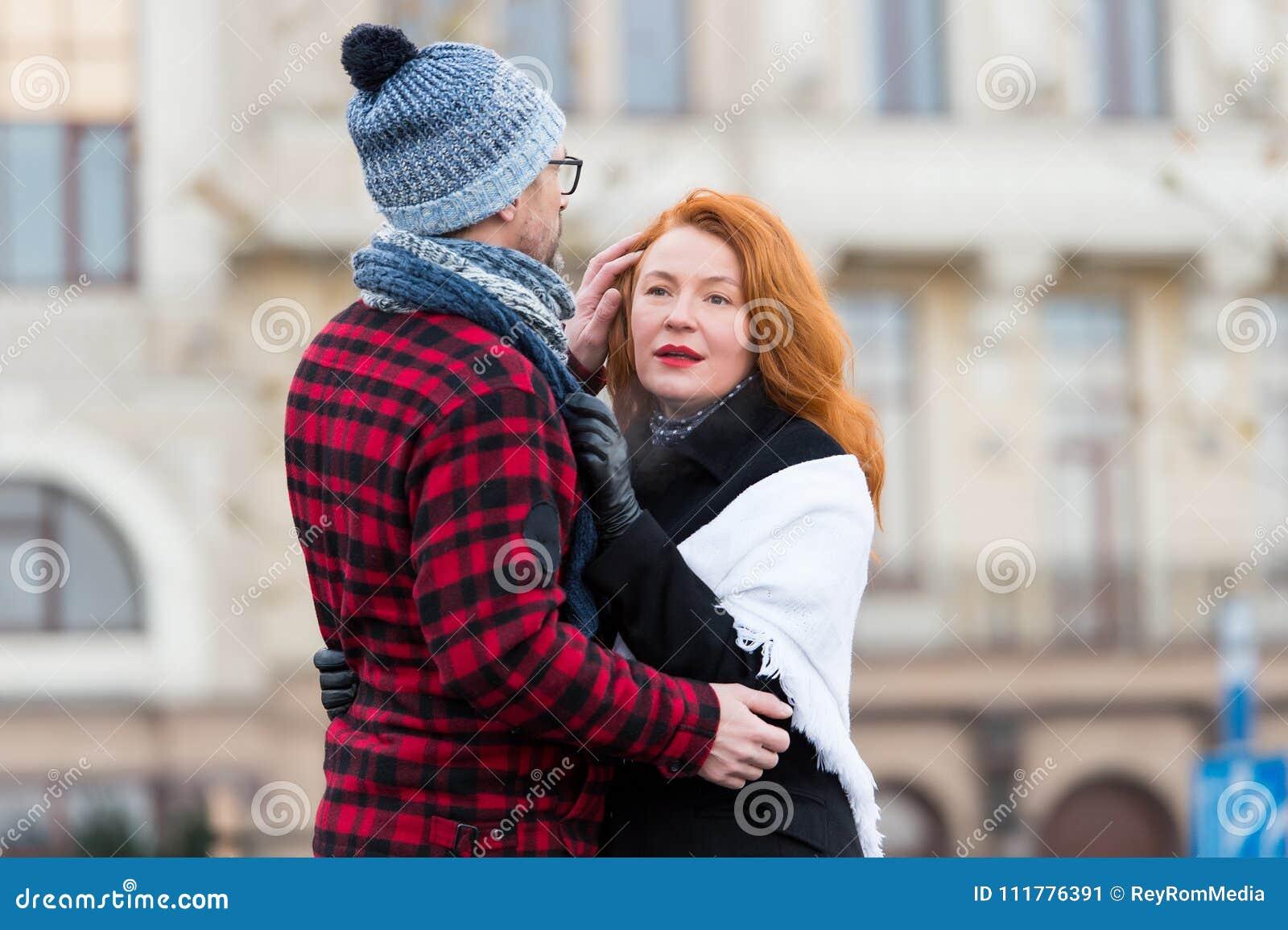 De gelukkige vrouw koestert de mens in hoed op de straat Gelukkig paar die op de stadsachtergrond koesteren Sensuele donkerbruine