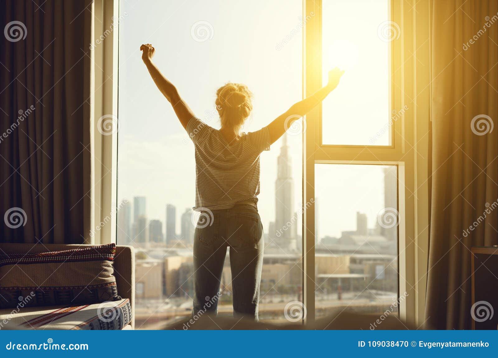 De gelukkige vrouw rekt en opent gordijnen bij venster in ochtend uit