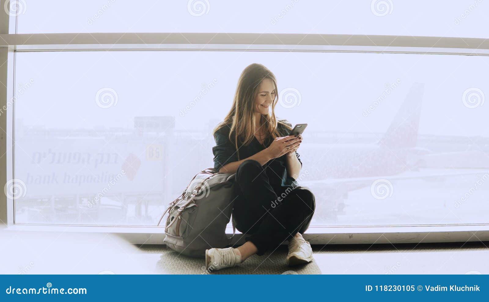 De gelukkige vrouw zit met smartphone door luchthavenvenster Kaukasisch meisje met rugzak die boodschapper app in terminal gebrui