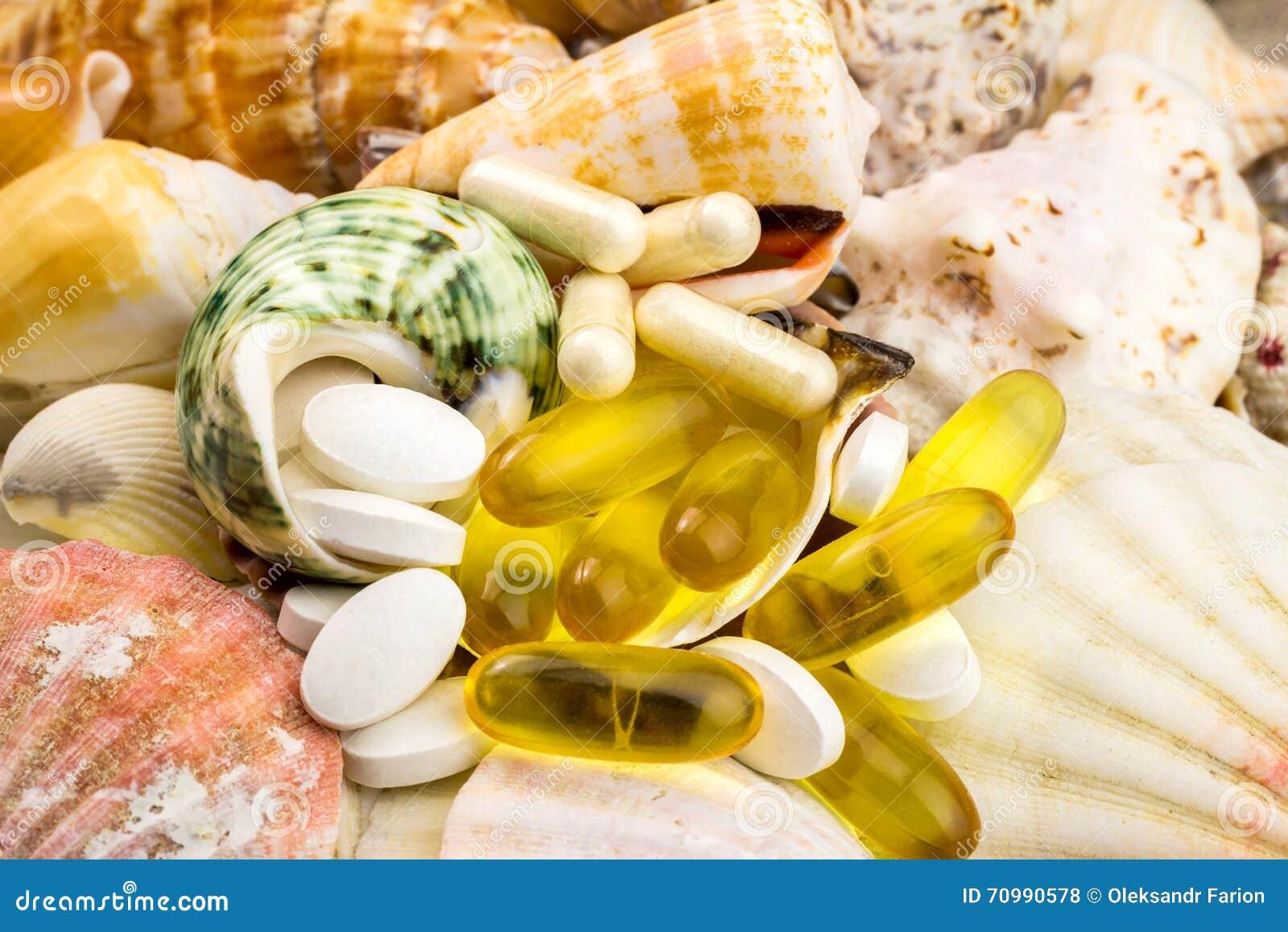 De gemengde pillen van het natuurvoedingsupplement op de mooie zeeschelpenachtergrond