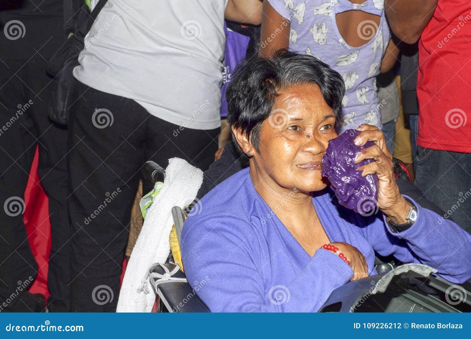 De gerijpte vrouw kreeg een handvol van kleverige die rijstcake aan mensen tijdens Chinese Maannieuwjaarviering wordt weggegeven