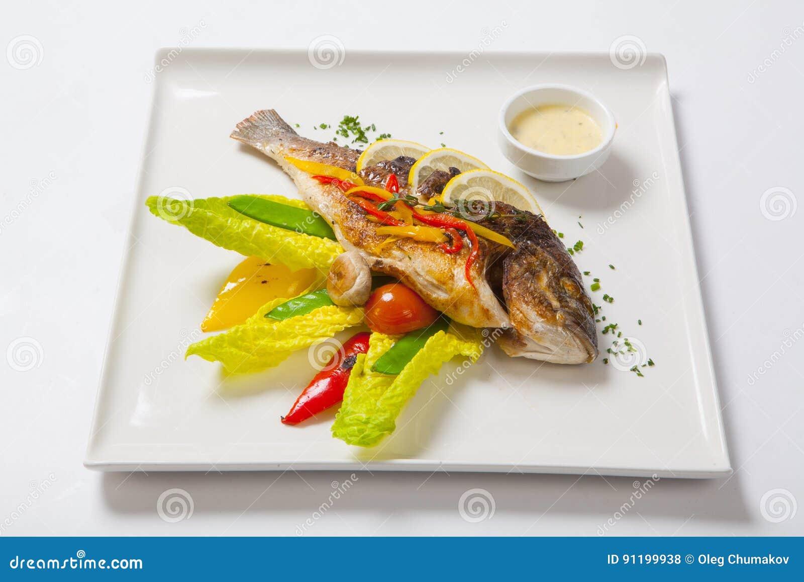 De geroosterde gehele die vissen verfraaiden met bladeren van sla en kersentomaat, met knoflooksaus worden gediend Gebraden gehel
