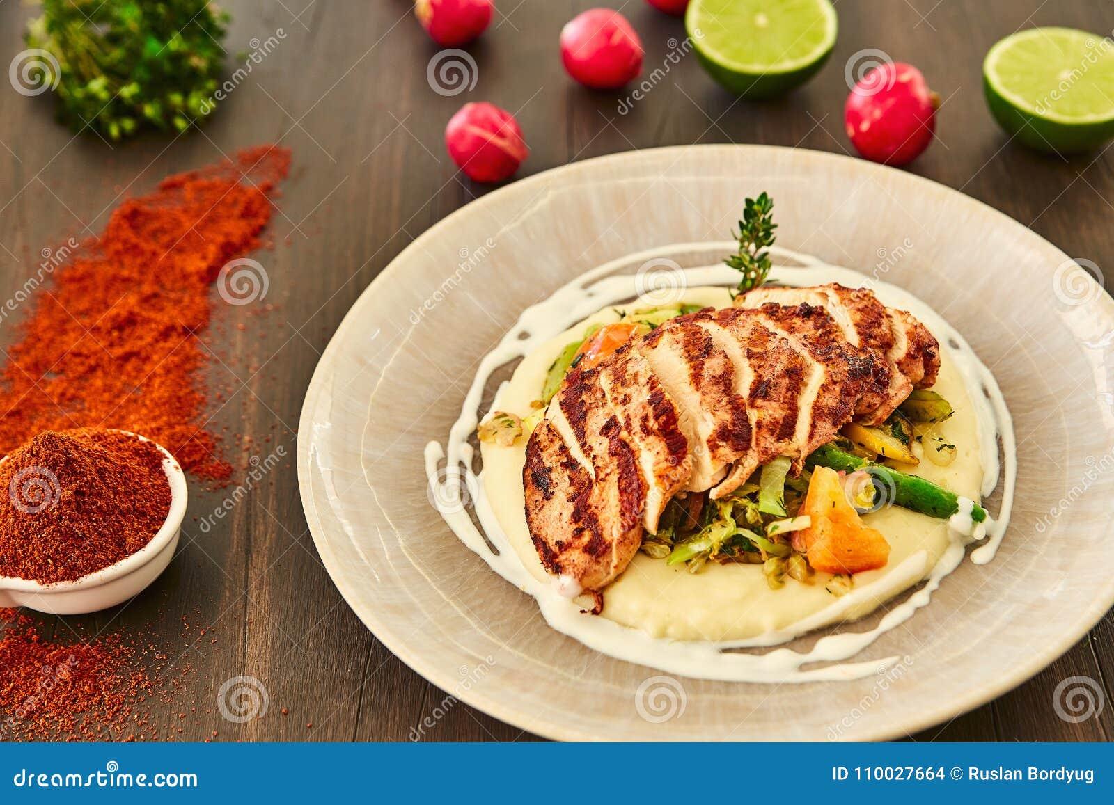 De geroosterde kippenfilet wordt gesneden in plakken op een kussen van fijngestampte aardappels met groenten - ui, knoflook, pepe