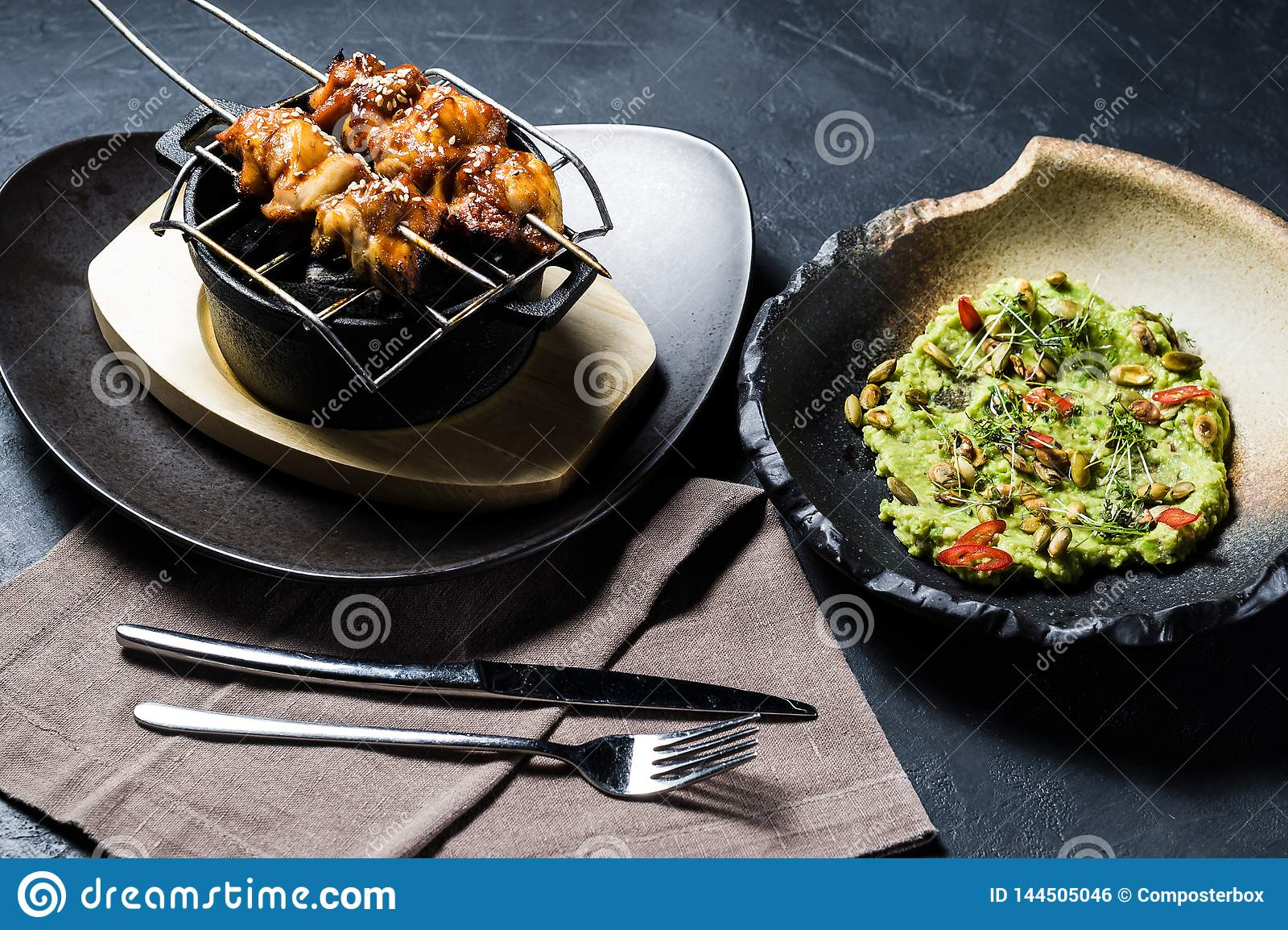 De geroosterde kippenkebab met guacamole versiert, donkere achtergrond, hoogste mening