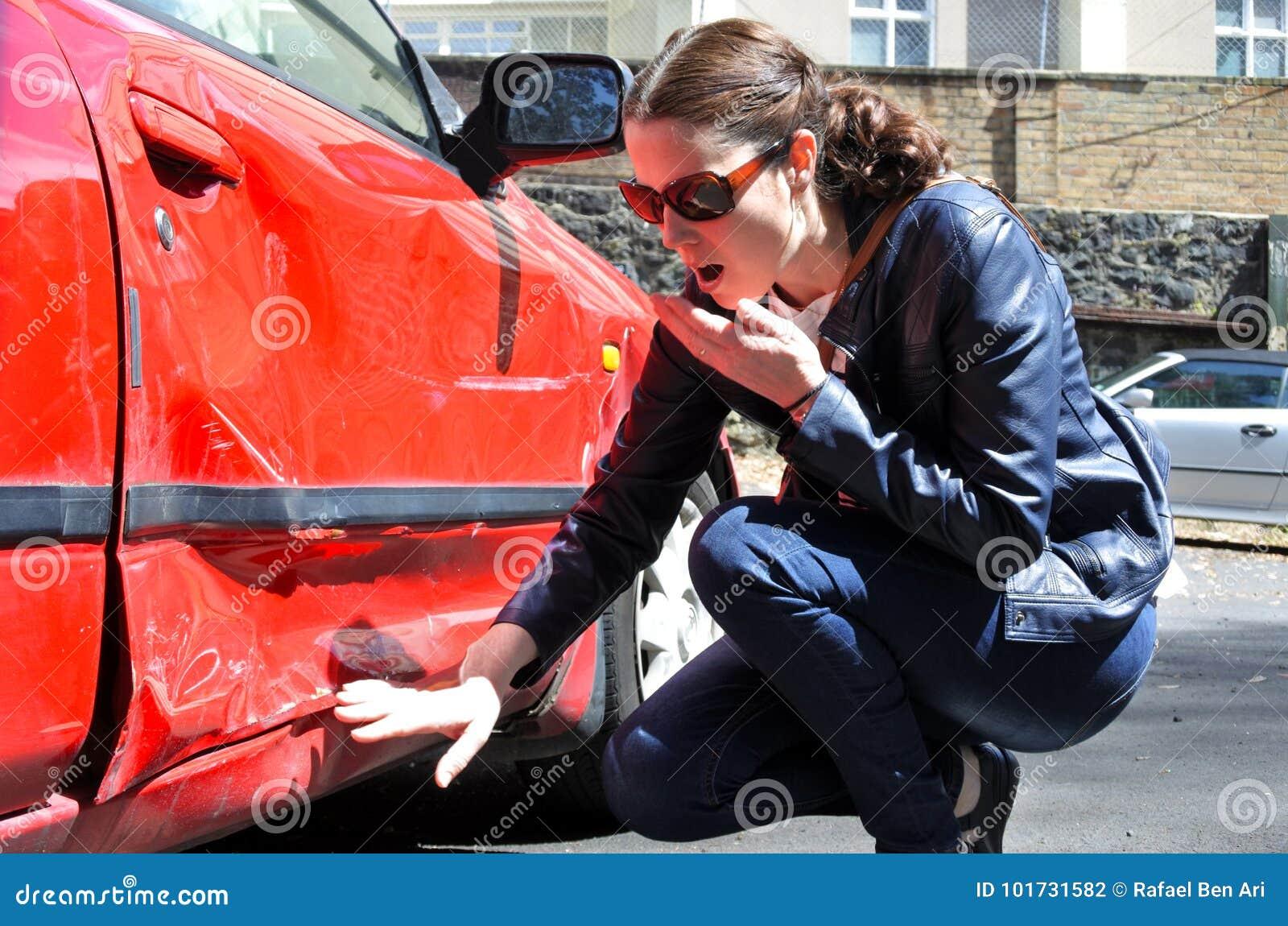 De geschokte vrouw kijkt een schade van haar auto