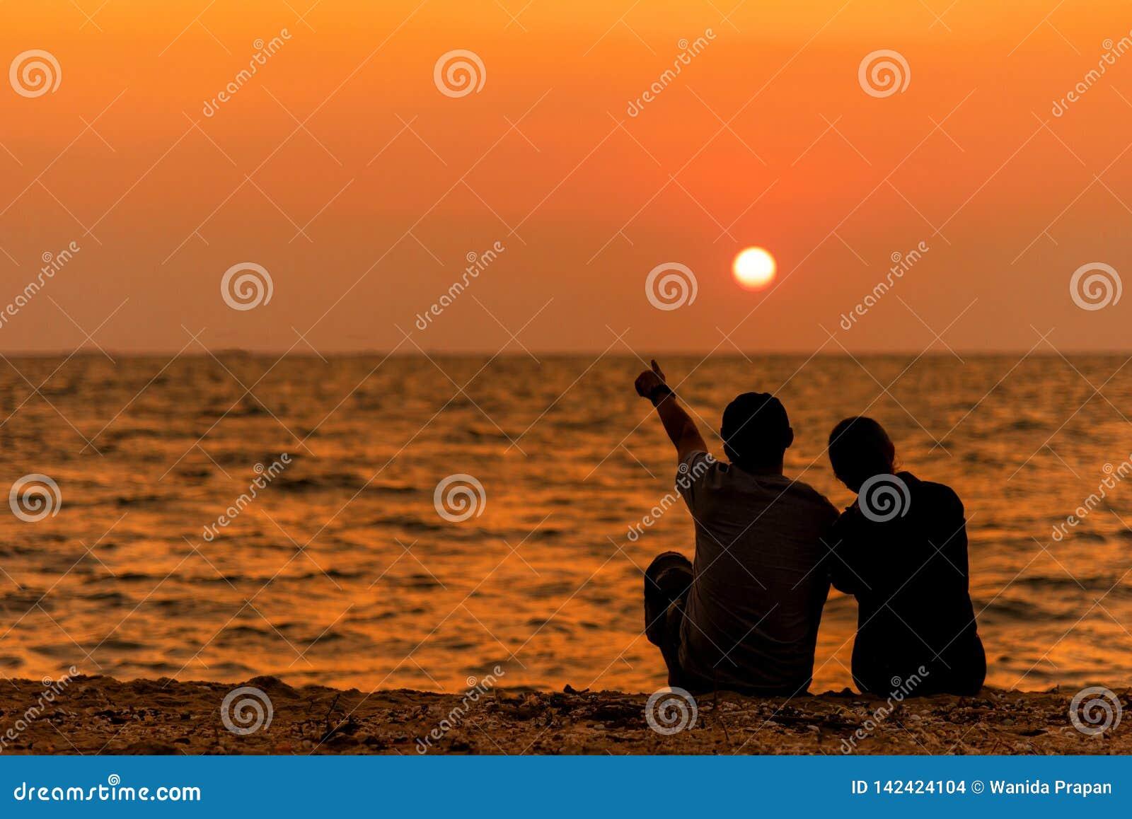 De gesilhouetteerde paarzitting, en ontspant op strand in liefde en omhelst, zonsondergang in het strand