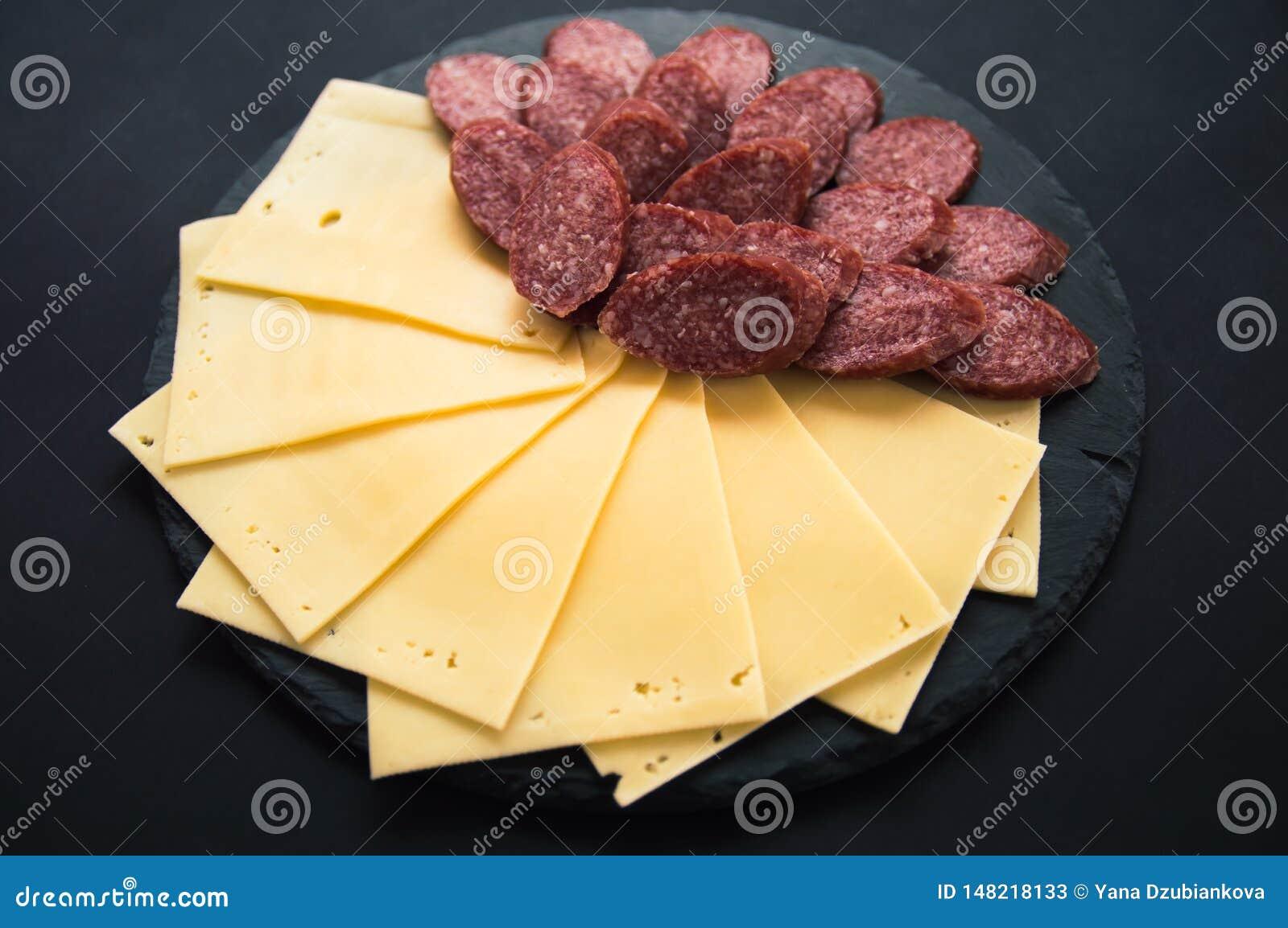 De gesneden kaas en salamiworst ligt op een ronde steen zwarte raad Kaasplakken op een zwarte achtergrond Worst op een ronde word