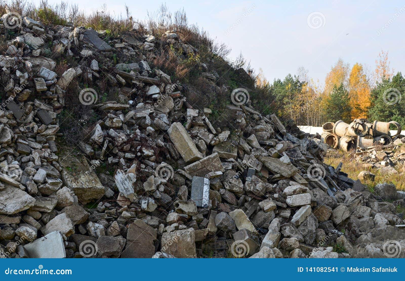 De gewapend beton blokken van het bouwafval en roestige montage De bouw puin Ecologie, globalisering Concrete plakken, stortplaat