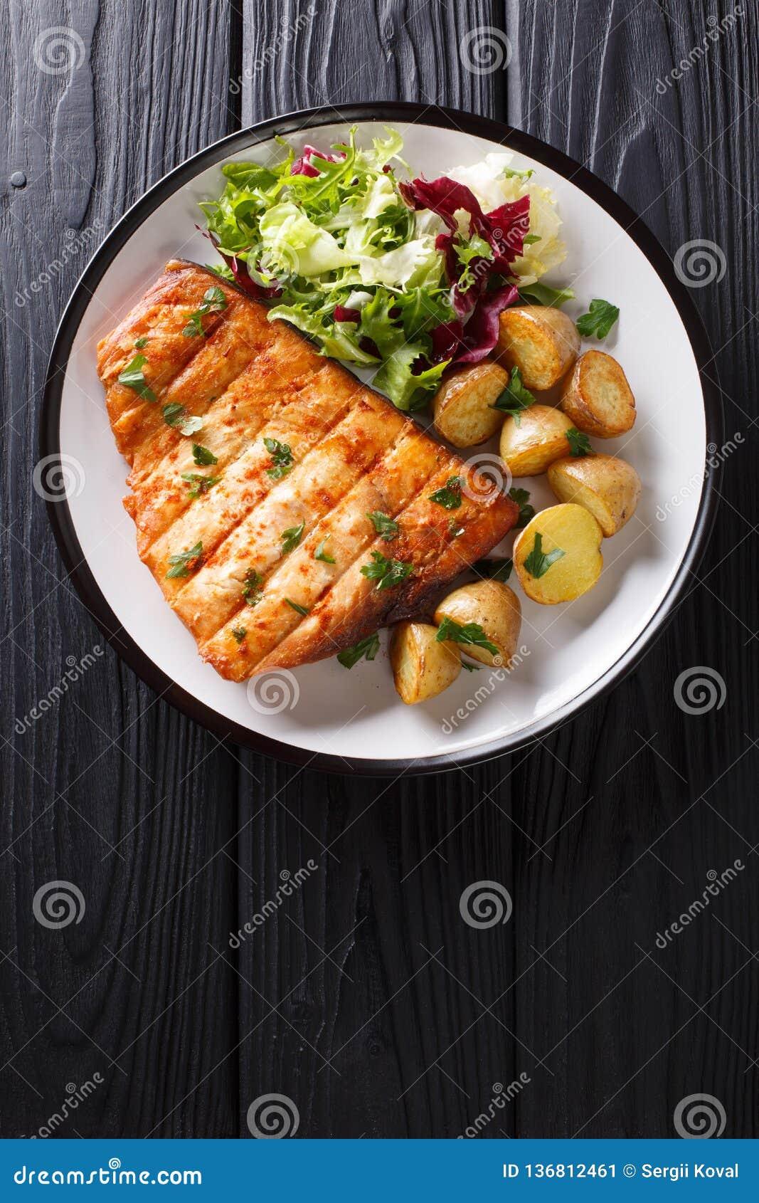 De gezonde lunch roosterde zwaardvissenfilet met gebraden aardappels en vers saladeclose-up op een plaat Verticale hoogste mening