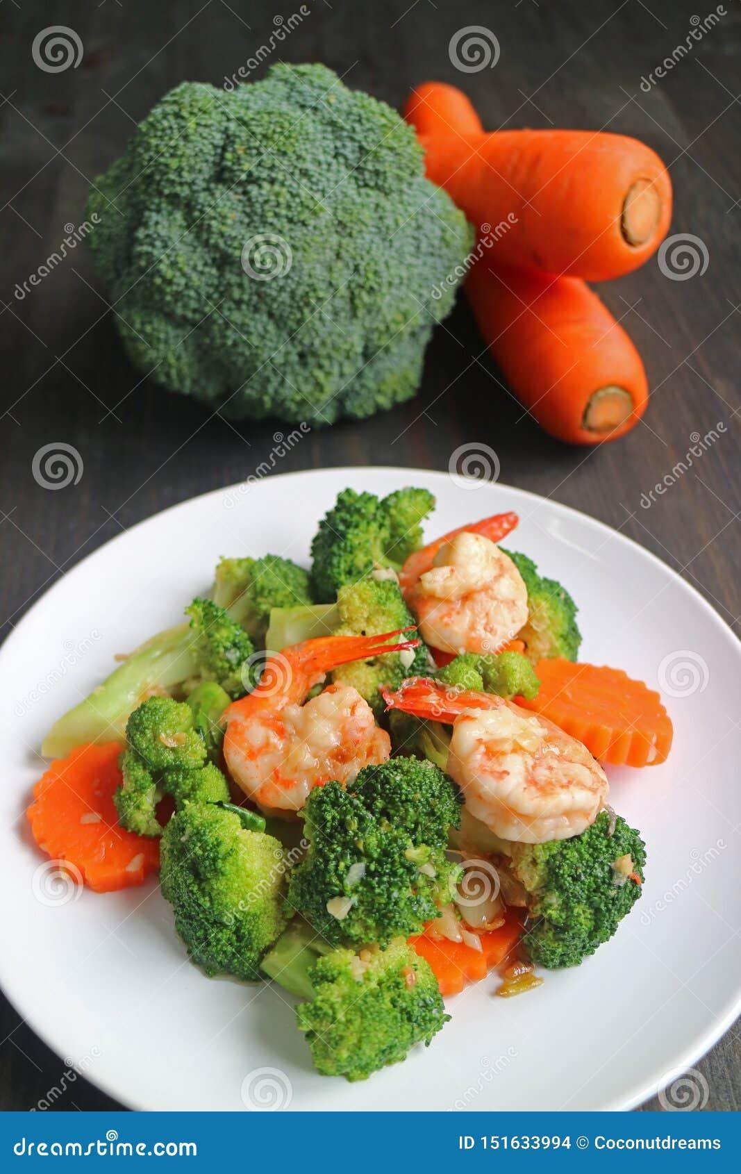 De gezonde schotel van garnaal beweegt gebraden die met broccoli en wortel op witte plaat worden gediend