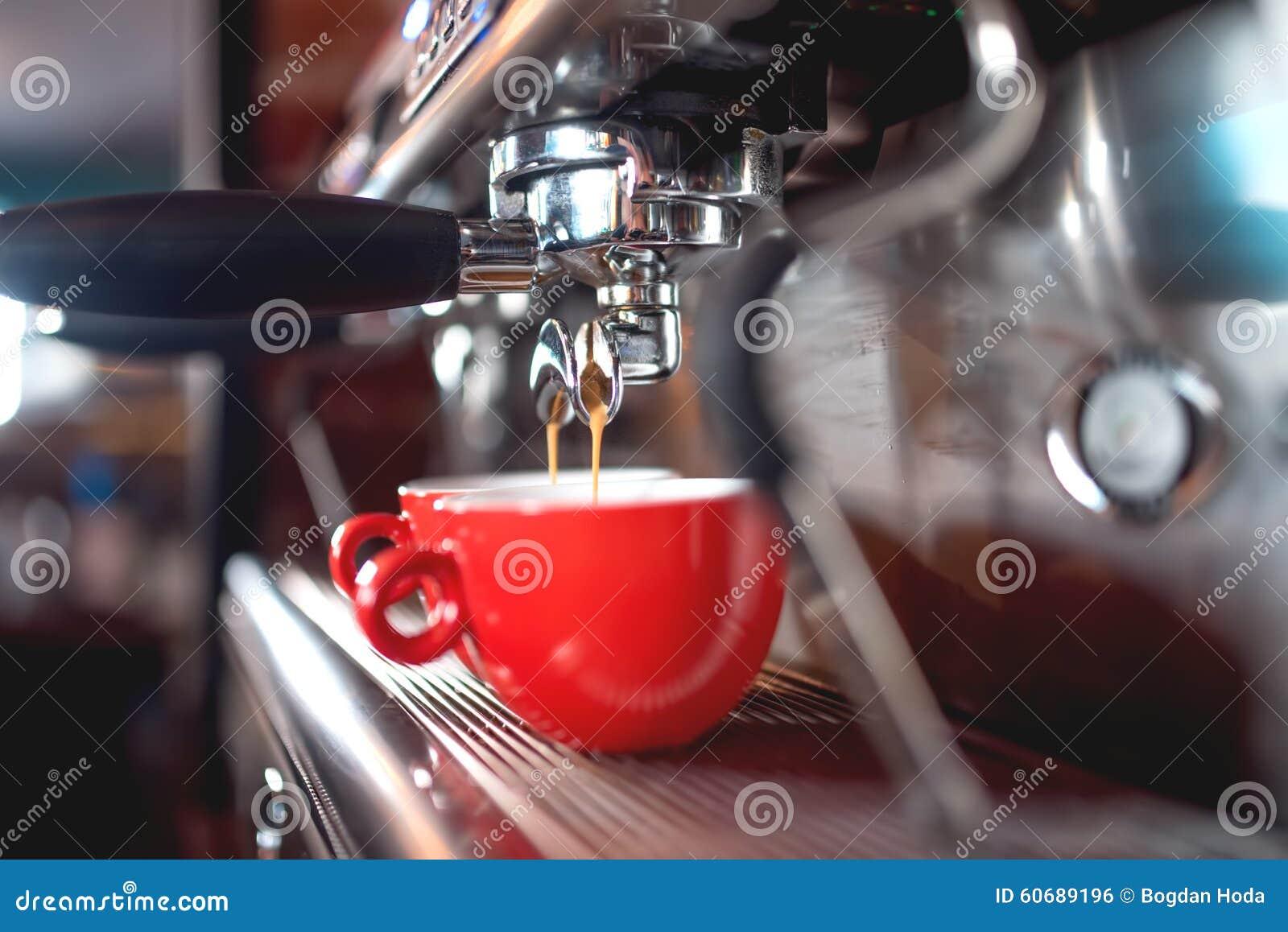 De gietende koffie van de espressomachine in koppen bij restaurant of bar Baristaconcept met machines, stamper, koffie en hulpmid