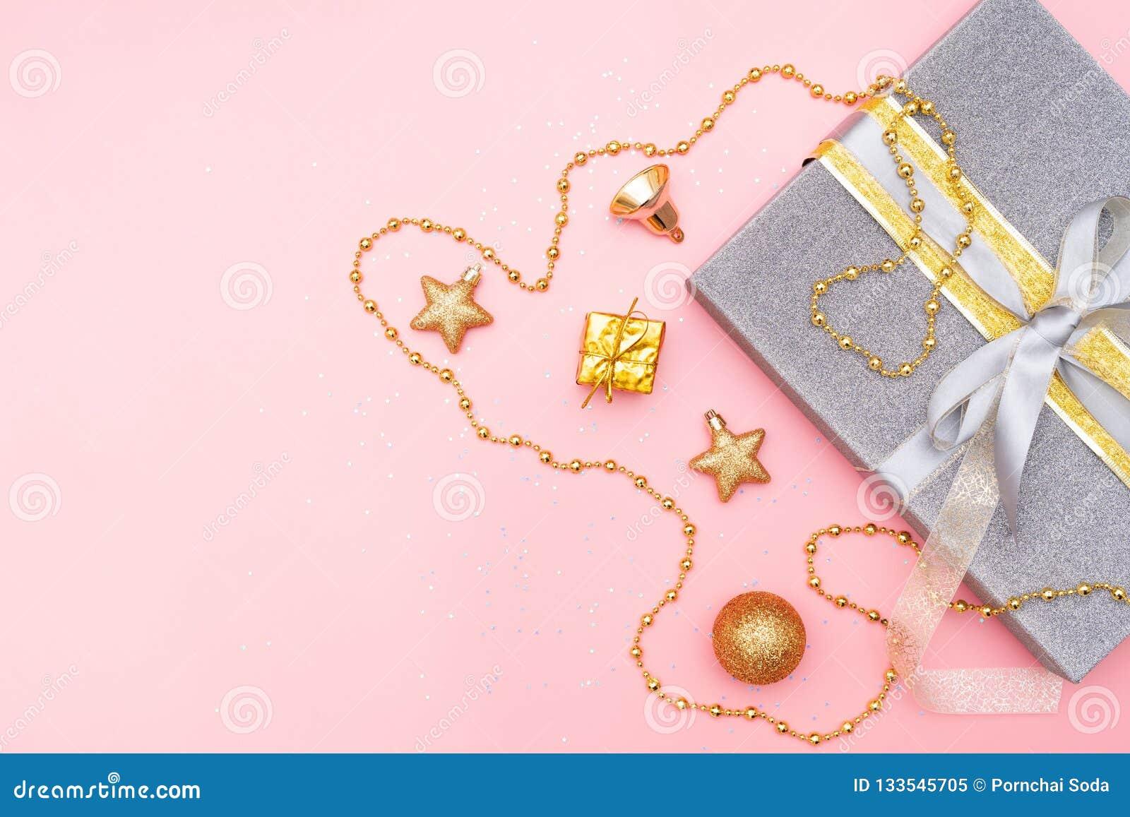 De giftendozen of stelt dozen met gouden bogen, ster en bal op roze achtergrond voor verjaardag, Kerstmis of huwelijksceremonie v