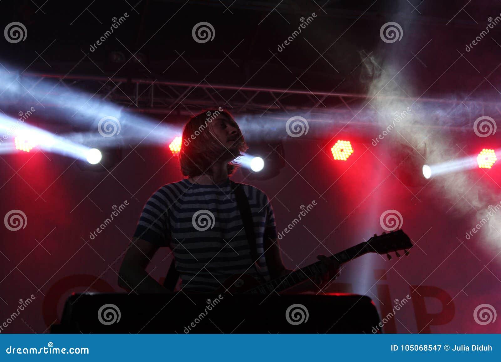 De gitarist van het rotsoverleg in lichtenenergie van Oekraïense band Antitila